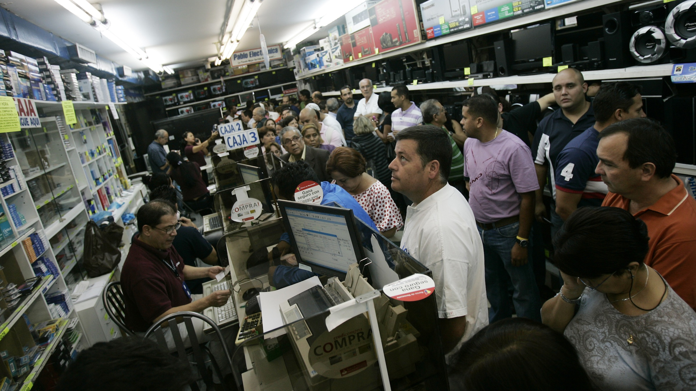 People crowd to buy electrical appliances at a shop in Caracas, Monday, Jan. 11, 2010. The currency's official exchange rate had been held steady by the government at 2.15 bolivars to the dollar since the last devaluation in March 2005. Venezuela's President Hugo Chavez said the bolivar will now have two government-set rates: 2.6 to the dollar for transactions deemed priorities by the government, and 4.3 to the dollar for other transactions. (AP Photo/Leonardo Ramirez)