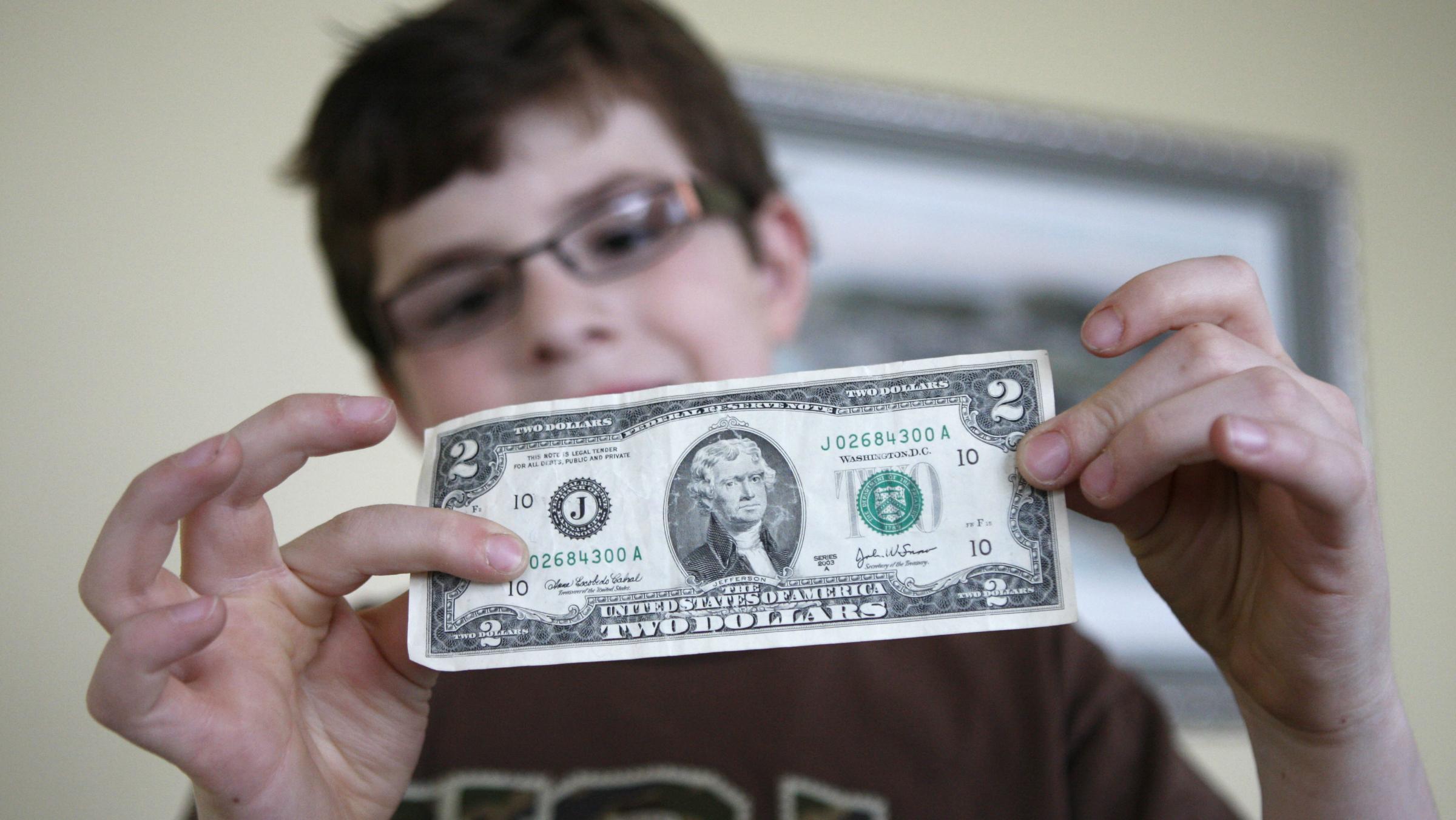 A boy holding a 2-dollar bill.