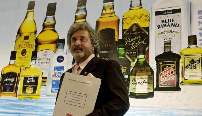 Vijay Mallya, Chairman UB Group and Shaw Wallace, poses in front of a poster showing different liquor brands of his company's spirits business United Spirits Ltd.