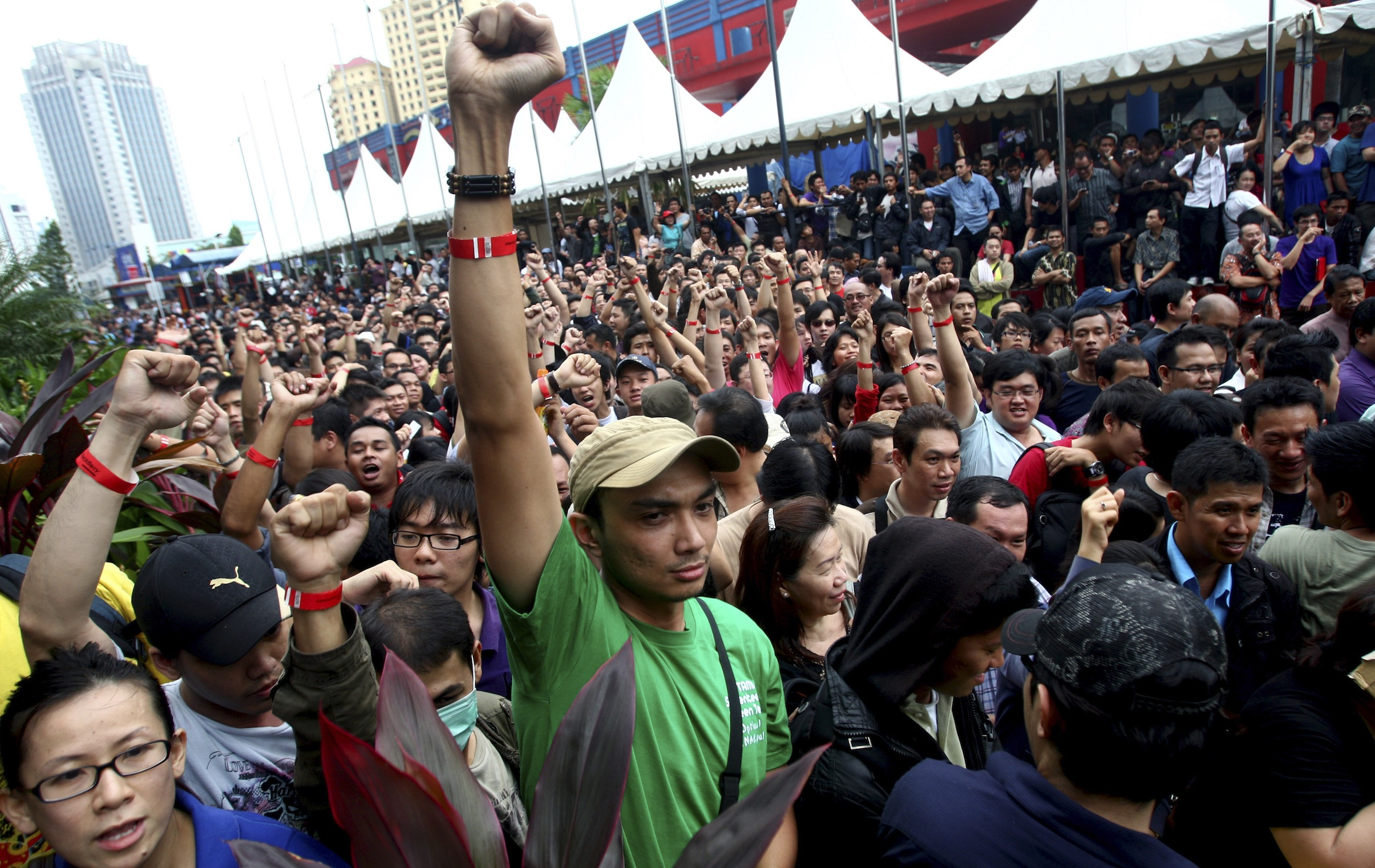 Impatient Indonesians raise their fists to show their 'priority' wrist bands as they queue up to buy the new BlackBerry 9790 at discounted price for the first 1,000 buyers outside a shopping mall in Jakarta, Indonesia, Friday, Nov. 25, 2011. Thousands of Indonesians jammed into a glitzy shopping mall Friday to get hold of the first BlackBerry Bold 9790s being sold worldwide.