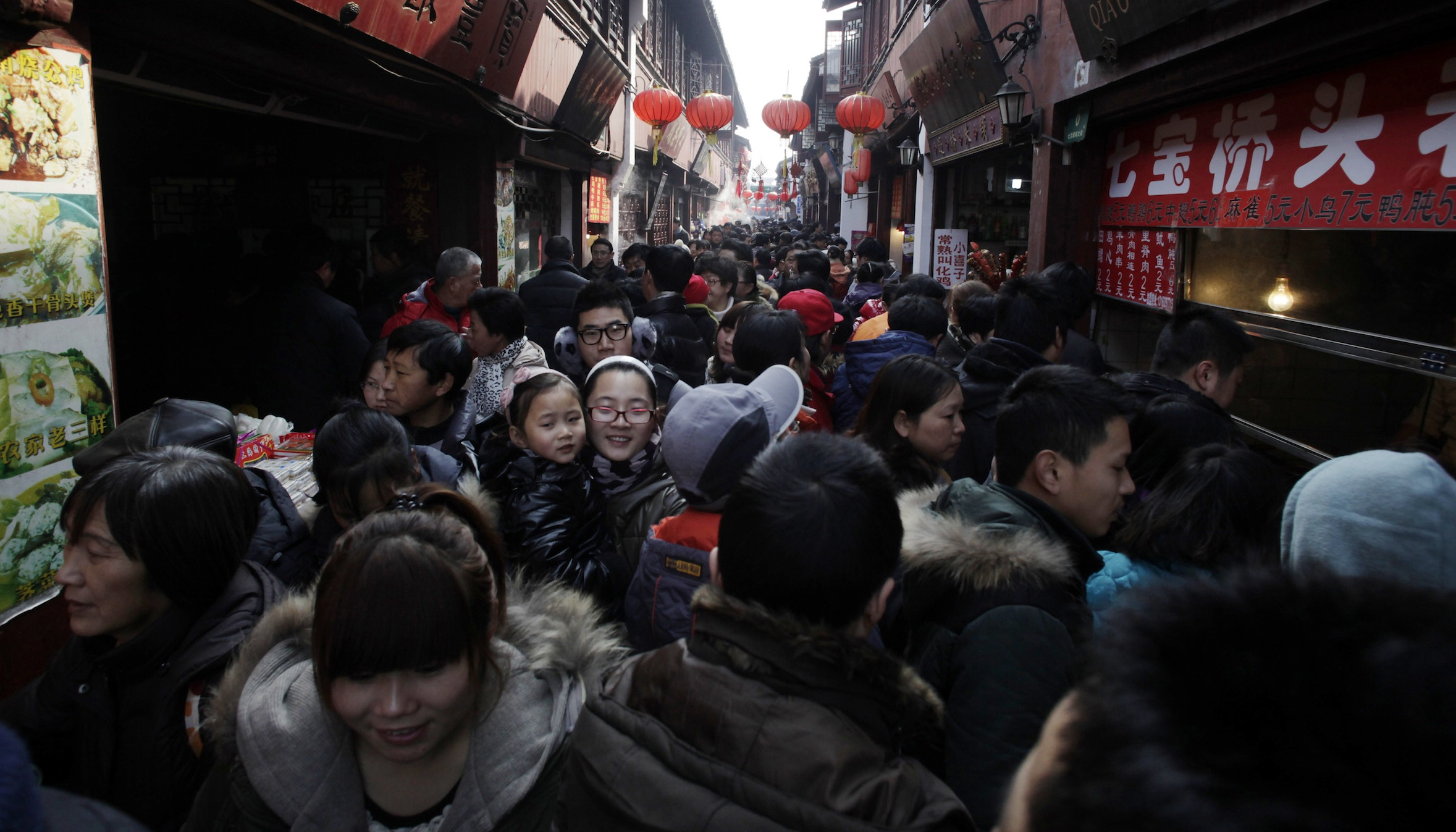 Visitors crowd a shopping street on the third day of the Chinese Lunar New Year Wednesday Jan. 25, 2012 in Shanghai, China. (AP Photo/Eugene Hoshiko)