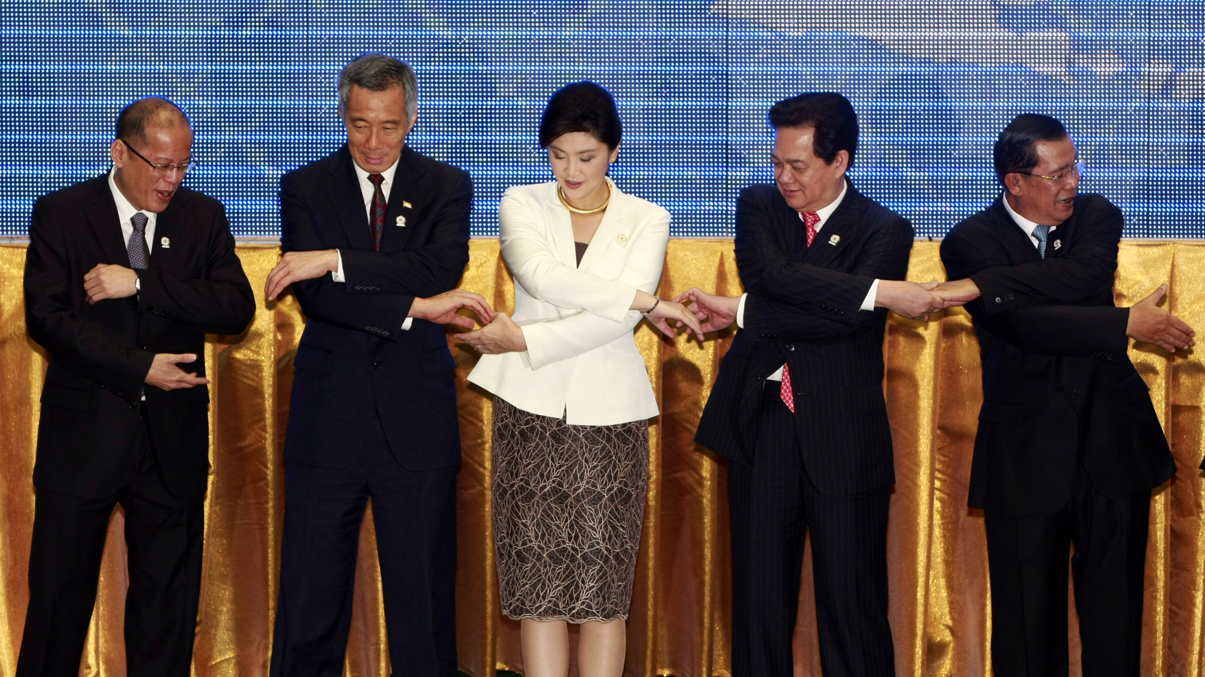 FILE - In this April 3, 2012 file photo, leaders from the Association of Southeast Asian Nations (ASEAN) from left, Philippines' President Benigno Aquino III, Singapore Prime Minister Lee Hsien Loong, Thailand's Prime Minister Yingluck Shinawatra, Vietnam's Prime Minister Nguyen Tan Dung and Cambodia's Prime Minister Hun Sen shake hands for a group photo during the opening ceremony of the 20th ASEAN Summit in Phnom Penh, Cambodia. Although Asia leads the world in terms of the number of years women have governed as heads of state, and currently has four women leaders it is still extremely underrepresented in top leadership positions, the Asia Society said in a report issued Thursday, April 18, 2012. (AP Photo/Apichart Weerawong, File)