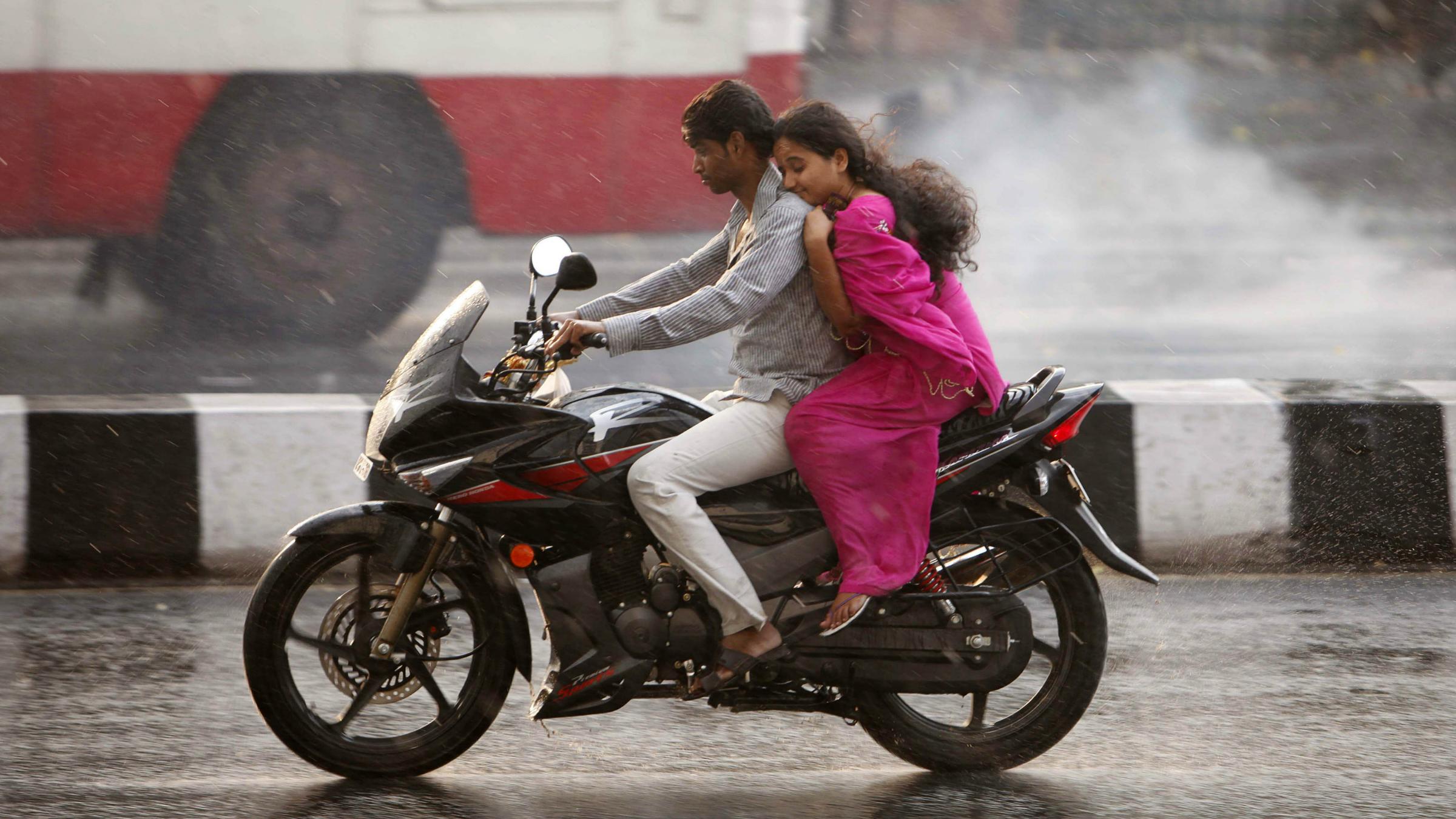 A couple rides a bike through rainfall in Hyderabad, India, Friday, April 6, 2012. (AP Photo/Mahesh Kumar A.)