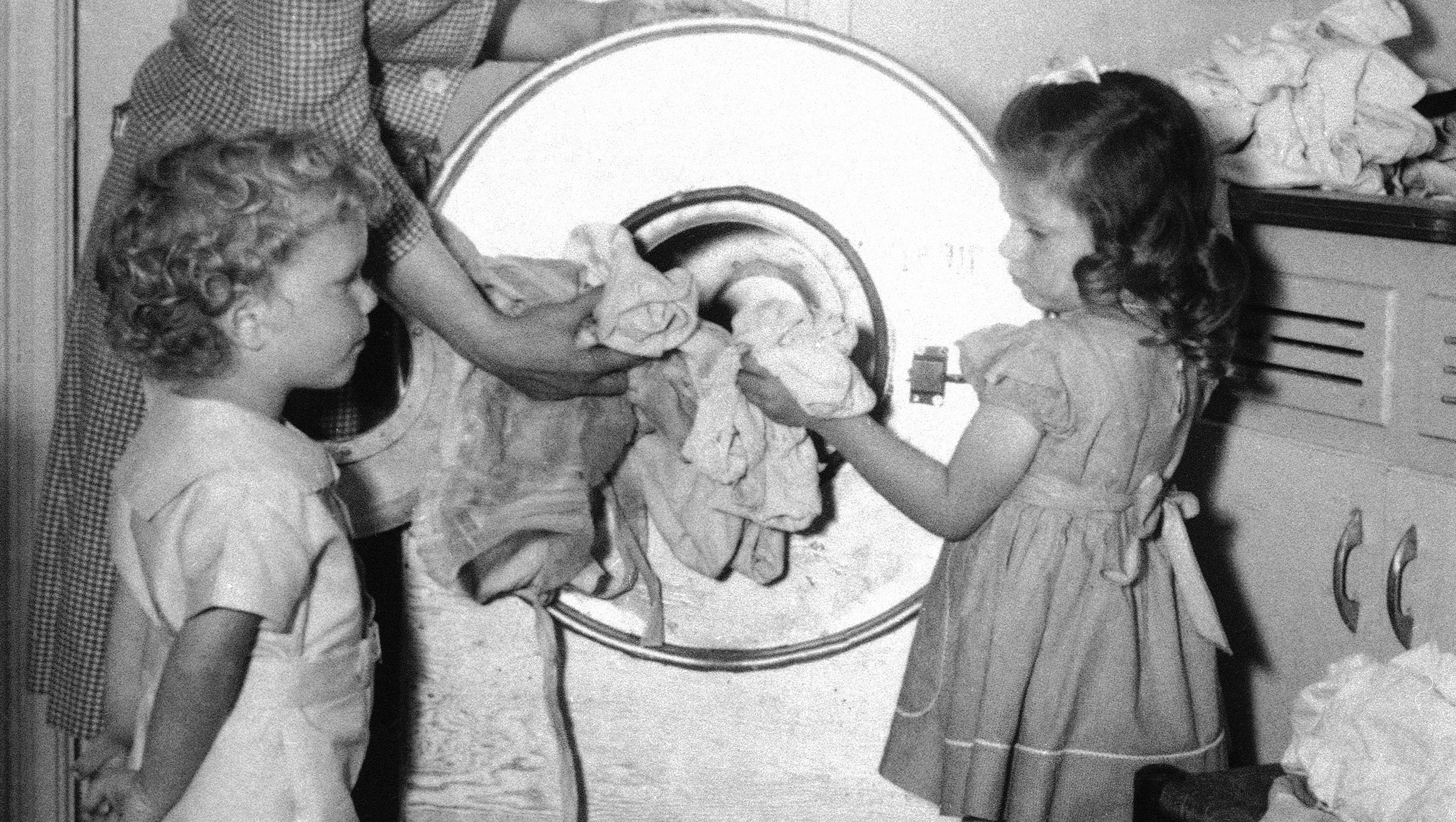 Mrs. Coy and daughter Ellen Hays stuff the week's soiled clothes into this washing machine in Marietta, GA. on August 26, 1945, which father Coy, production worker on Superfortresses, built from $6.50 worth of B-29 scrap plus a motor of his own. Three-year-old Jim Coy III looks on. (AP Photo)