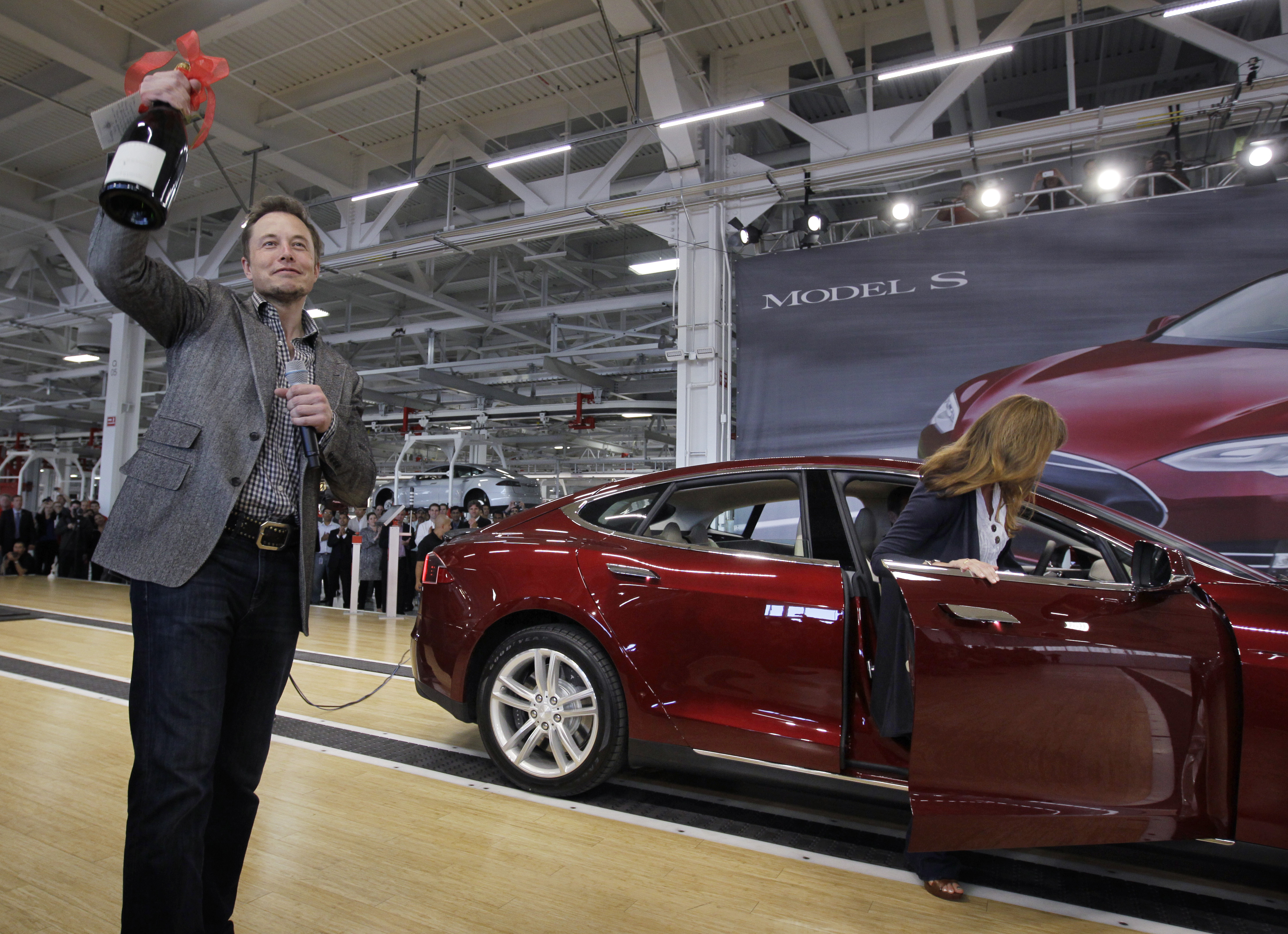 In this June 22, 2012 file photo, Tesla Motors Inc. CEO Elon Musk holds up a bottle of wine given as a gift from one of their first customers, right, during a rally at the Tesla factory in Fremont, Calif. Tesla Motors Inc. on Wednesday, July 25, 2012 said that its second-quarter net loss nearly doubled as it invested heavily to launch its second vehicle, the Model S. (AP Photo/Paul Sakuma, File)