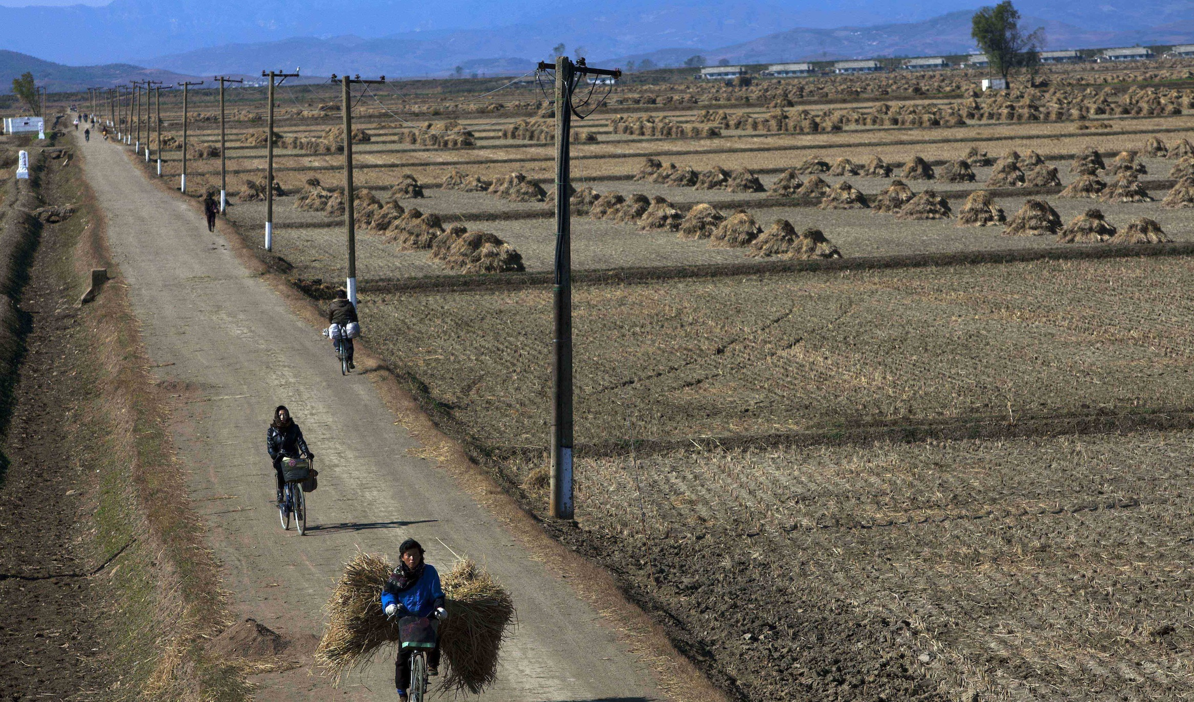 In this Tuesday, Oct. 25, 2011 photo, North Korean farmers pass along a road past farm fields at a collective farm near the town of Sariwon, North Korea. In a landmark shift after three years of tensions, the United States is poised to announce in the coming days its first significant donation of food aid to North Korea _ a small but symbolic offer that is expected to pave the way for long-stalled discussions on dismantling Pyongyang's nuclear program.