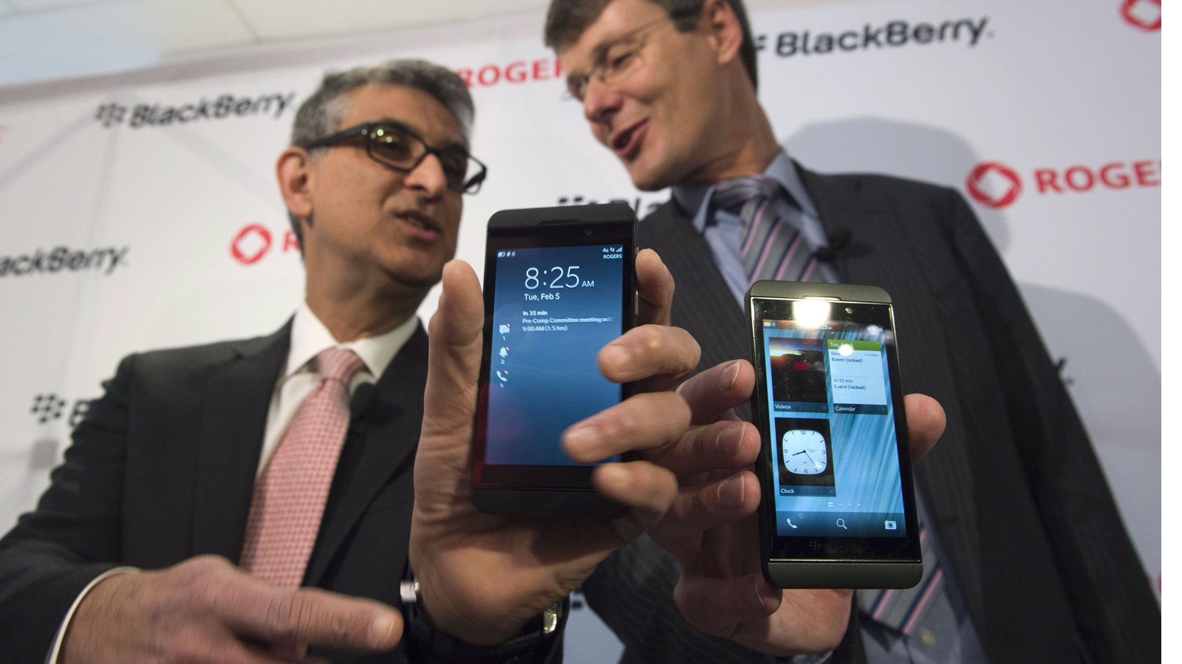Blackberry President and CEO Thorsten Heins, right, and Rogers Communications President and CEO Nadir Mohamed show off their Blackberry Z10 devices before presenting one to the first customer at a store in Toronto on Tuesday, Feb. 5, 2013. (AP Photo/The Canadian Press,Frank Gunn)