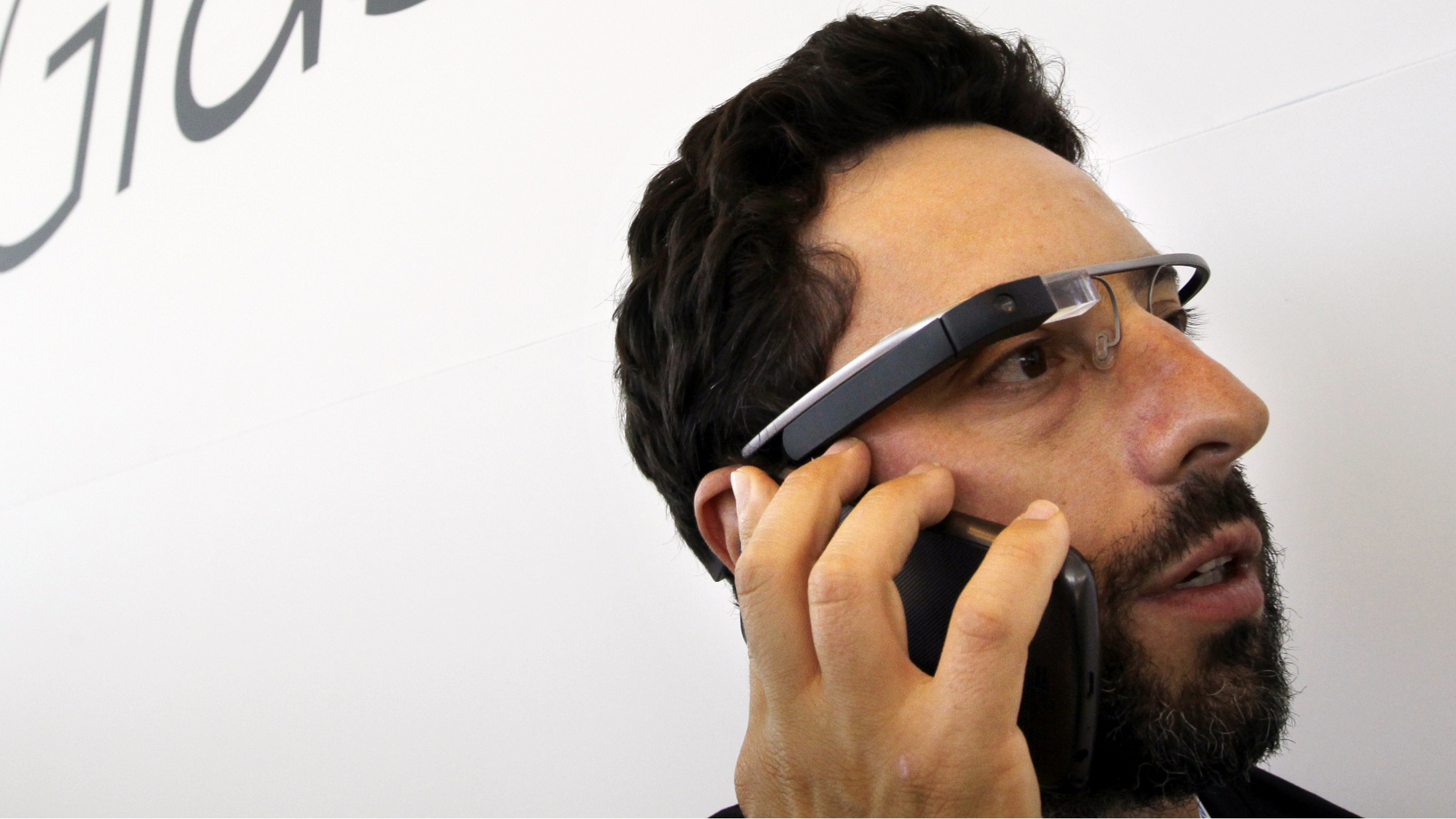 Google co-founder Sergey Brin talks on the phone as he wears Google's new Internet-connected glasses at the Google I/O conference in San Francisco, Wednesday, June 27, 2012. Google is making prototypes of the device, known as Project Glass, available to test. They can only be purchased — for $1,500 — at the conference this week, for delivery early next year.