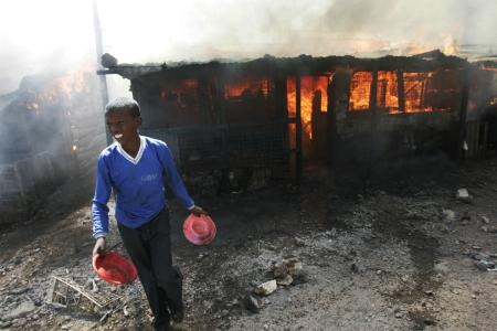 A young boy walks away from burning buildings after throwing sewage water on the fire, Wednesday, Jan. 2, 2008 during riots in the Mathare slum in Nairobi, Kenya.