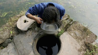 A Chinese villager drinks from a well on November 2, 2004 at Longshi, Chongqing, China. A group of eight cancer specialists were dispatched to the village by Chongqing municipality health authorities after 17 of the 500 villagers were diagnosed with different cancers for the last three years, and 14 of them died. The specialists, investigating the cause of the illness, are suspecting the water supplies.