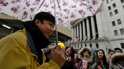 A Chinese tour guide entertains Chinese tourists in front of the New York Stock Exchange