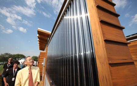 U.S. Energy Secretary Steven Chu tours the University of Maryland's entry in the U.S. Department of Energy Solar Decathlon, followed by students Scott Tjaden, left, and Jeff Rappaport, second from left, in Washington, D.C., Friday, Sept. 30, 2011. (Credit: Stefano Paltera/U.S. Department of Energy Solar Decathlon)