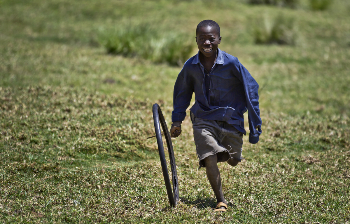 A young boy rolls an old bicycle tire with a wooden stick as a game, in Mawingu camp for the internally-displaced.