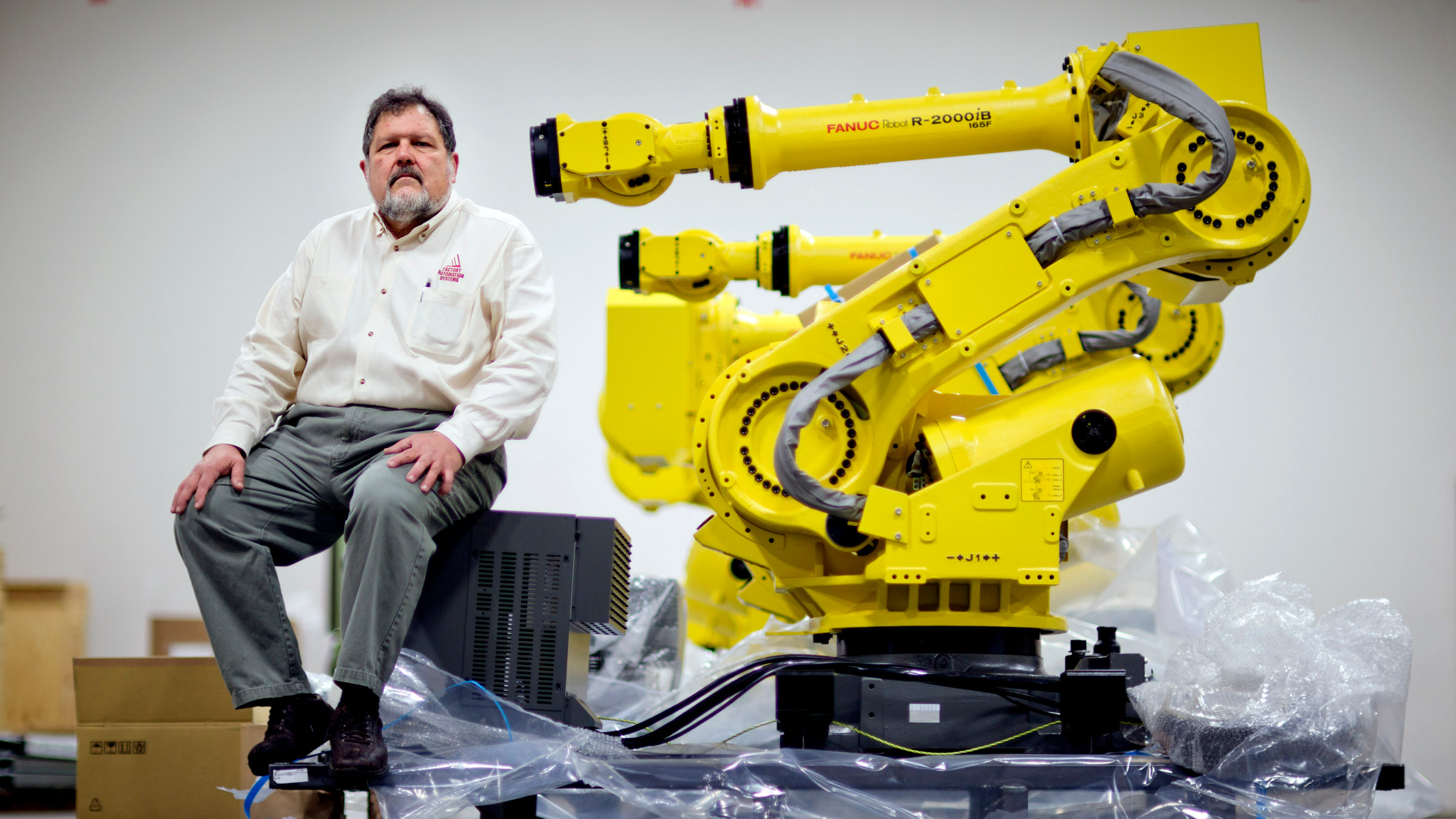 In this Jan. 15, 2013, photo, Rosser Pryor, Co-owner and President of Factory Automation Systems, sits next to a new high-performance industrial robot at the company's Atlanta facility.