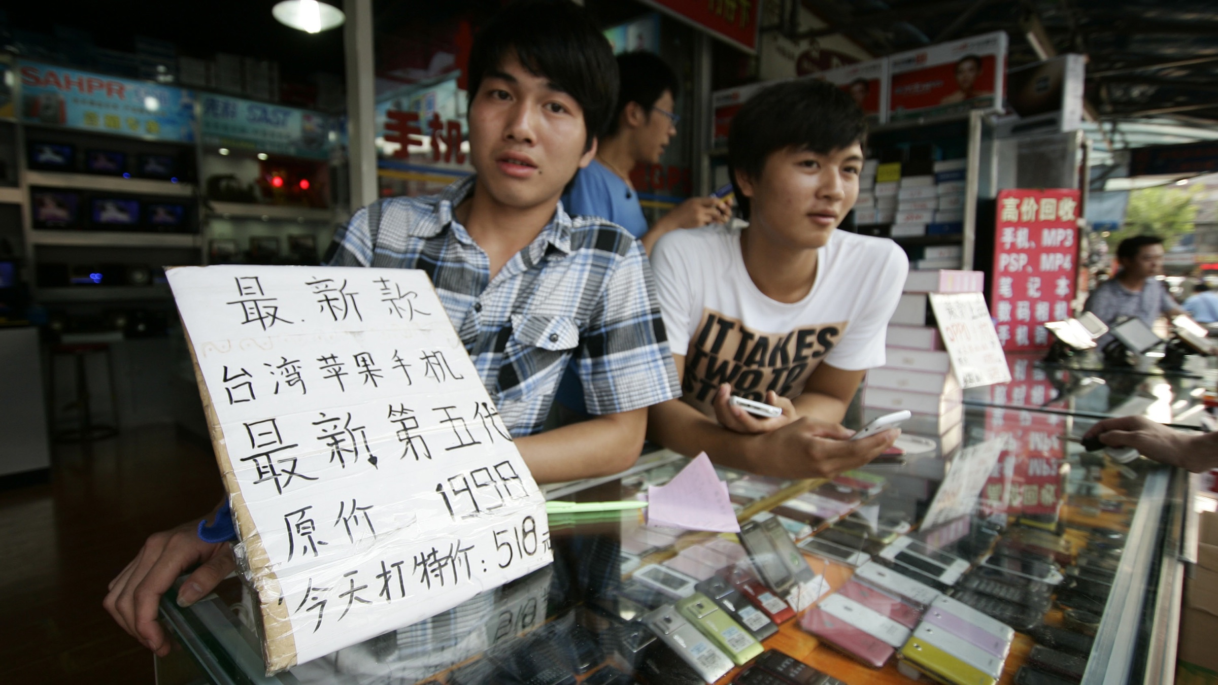 """Shop clerks sell fake iPhones at a mobile phone shop Sunday, Aug. 14 in Shanghai, China. A sales banner, left, written in Chinese reads: """"The latest iPhone 5."""" (AP Photo)"""