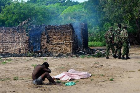 Security officers walk away as a man mourns next to the bodies of his wife and daughter, who were gunned down outside their house as they attempted to escape when suspected Orma raiders attacked their village of Kibusu in Kenya Thursday, Jan. 10, 2013.