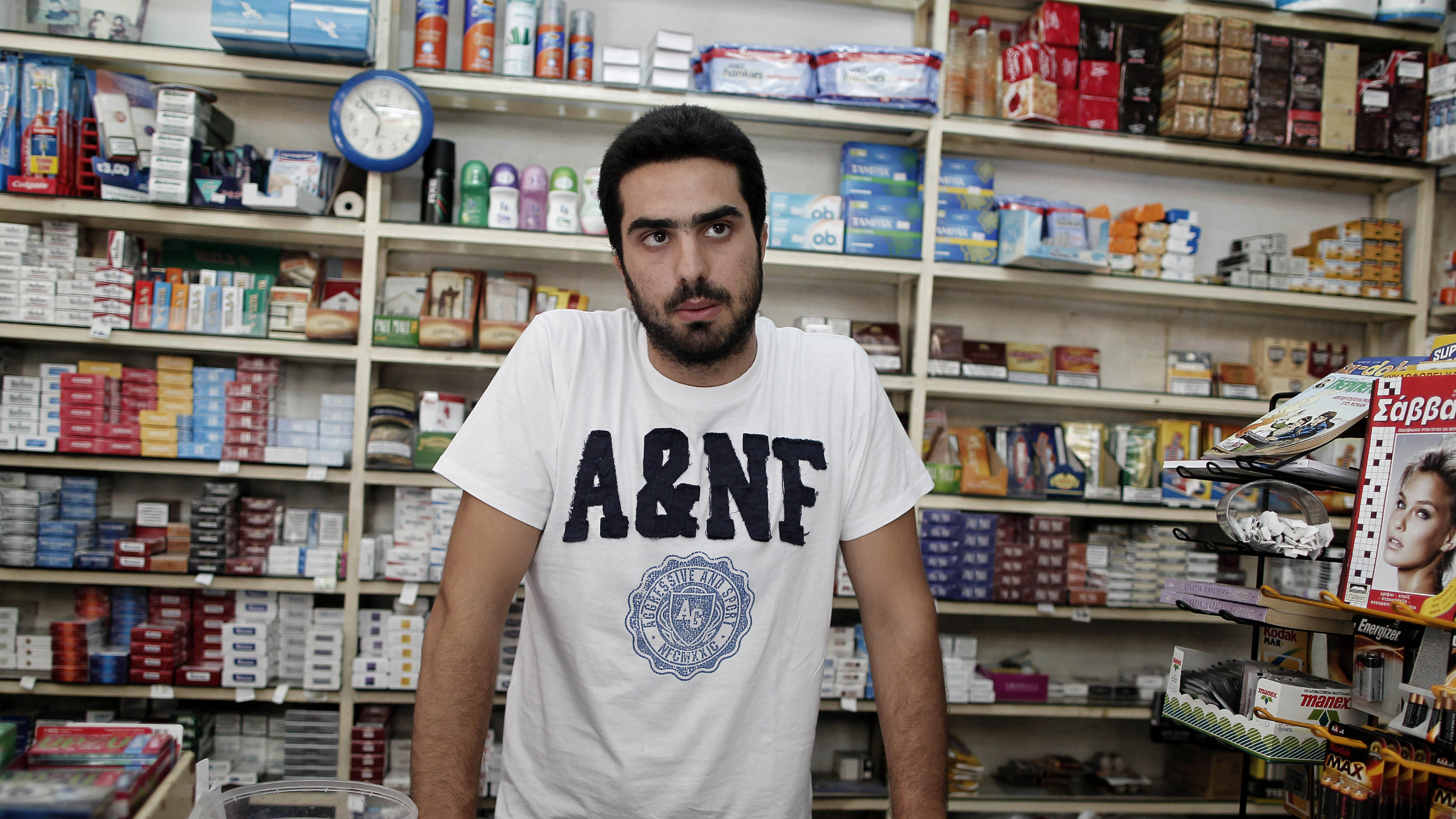 """Dimitris Dedoussis, 20, stands at the counter of his corner shop near Syntagma Square in central Athens, on Thursday, Aug. 23, 2012. As Greek Prime Minister Antonis Samaras sets off around Europe to plead for more time to achieve the country's tough reform targets, austerity-weary Greeks are bracing for new pain but mostly expect to stay in the 17-nation eurozone, come what may. Dedoussis said planned new cutbacks would have severe consequences on Greece's battered middle class, adding that he expects protests sooner or later because people won't be able to cope. He said he does not expect the debt-crippled country's partners will be able to kick Greece out of the currency union, and will instead """"seek ways of taking the last euro left in our pockets.""""(AP Photo/Dimitris Dedoussis, 20, stands at the counter of his corner shop near Syntagma Square in central Athens, on Thursday, Aug. 23, 2012. As Greek Prime Minister Antonis Samaras sets off around Europe to plead for more time to achieve the country's tough reform targets, austerity-weary Greeks are bracing for new pain but mostly expect to stay in the 17-nation eurozone, come what may. Dedoussis said planned new cutbacks would have severe consequences on Greece's battered middle class, adding that he expects protests sooner or later because people won't be able to cope. He said he does not expect the debt-crippled country's partners will be able to kick Greece out of the currency union, and will instead """"seek ways of taking the last euro left in our pockets.""""(AP Photo/Petros Giannakouris)Petros Giannakouris)"""