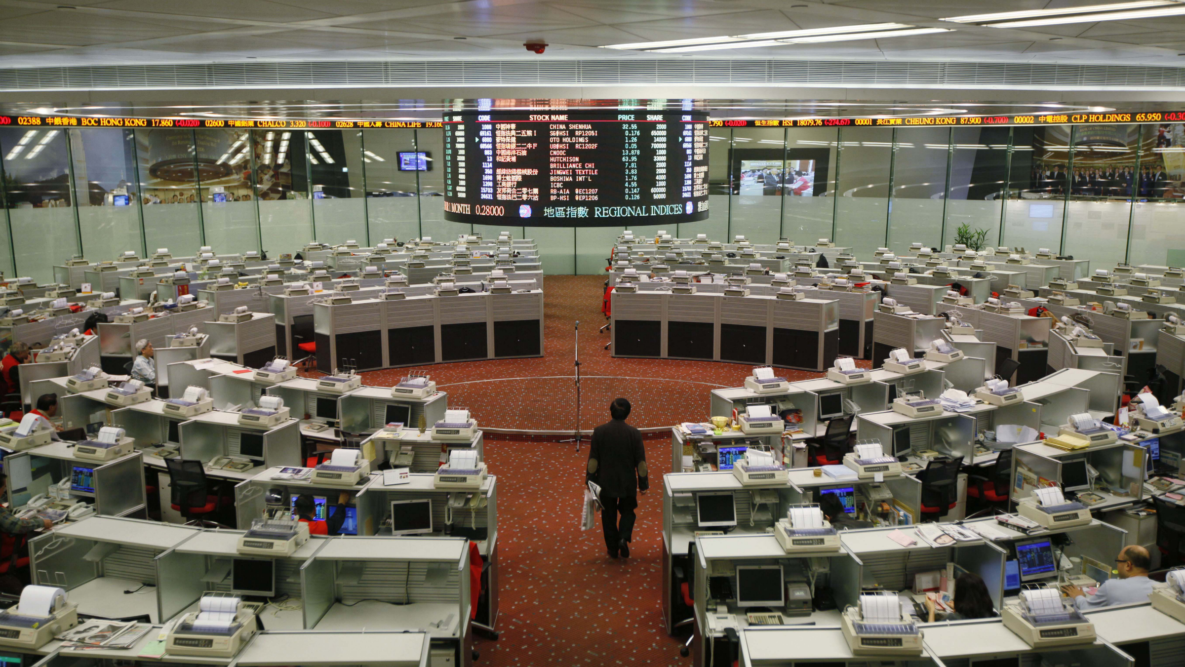 A floor trader walks at the Hong Kong Stock Exchange Thursday, Dec. 15, 2011. Asian stock markets fell Thursday as Japanese business confidence dropped and higher borrowing costs for Italy sparked worries over the ability of European governments to get a grip on their ever-burgeoning debts.