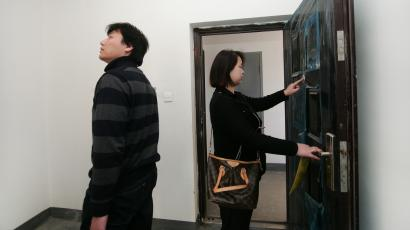 In this March 24, 2012 photo, Wang Zhen, right, and her husband Han Jiahang, left, check their room of new affordable housing complex in Hangzhou, China. The country's low-cost housing program is meant to provide decent accommodation for families priced out of the commercial real estate market and to help keep economic growth on track. But problems with financing, quality and corruption are plaguing the program. And for many, the prices are not low enough to offset disadvantages such as the out-of-the-way locations of the housing estates. (AP Photo)