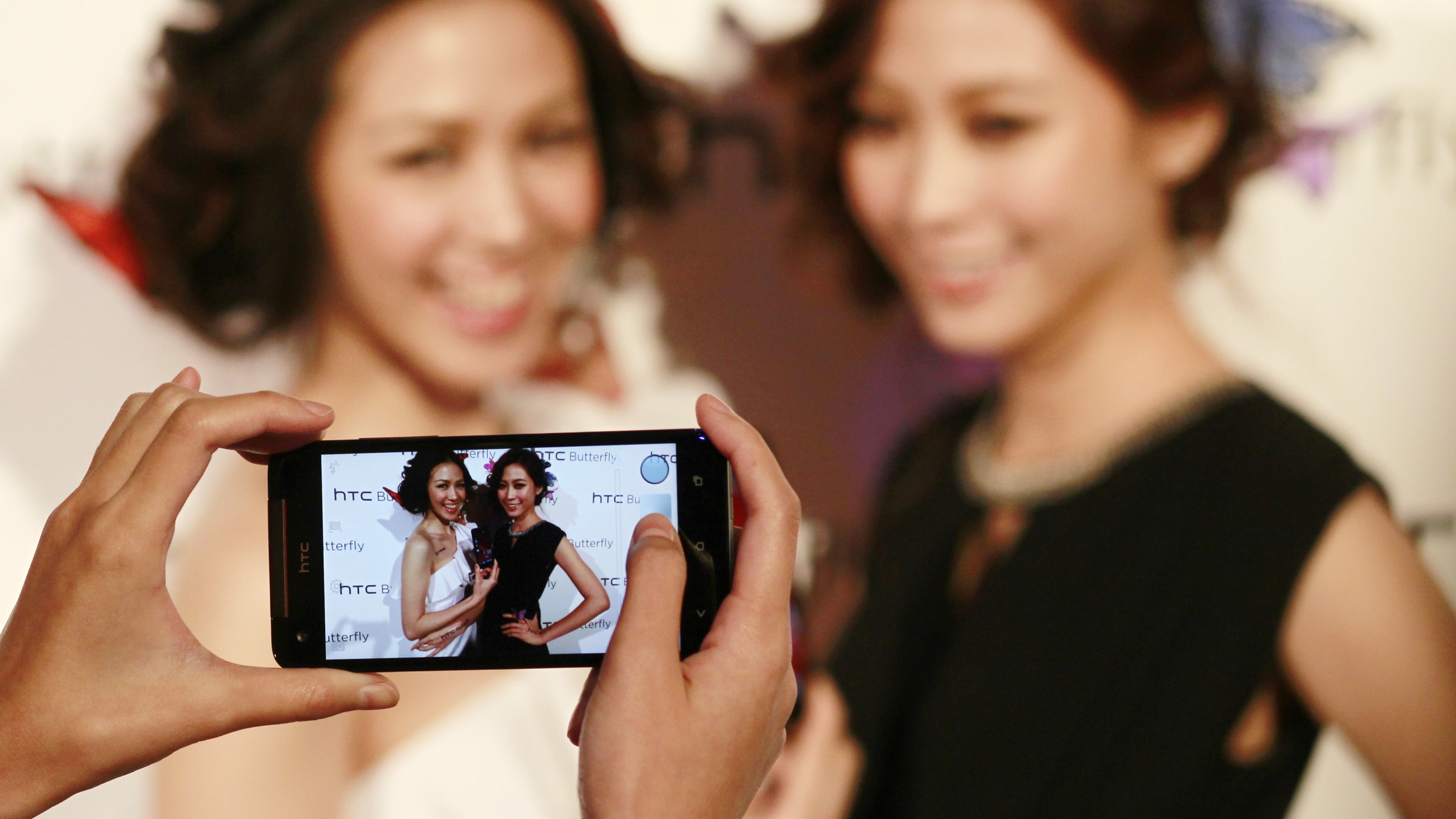 Models take photos with the new HTC J Butterfly smart phone, featuring a 5-inch Super LCD 3 display with 1920x1080 resolution, at a launch party in Taipei, Taiwan, Tuesday, Dec. 11, 2012. (AP Photo/Wally Santana)
