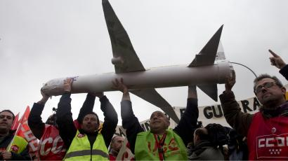 Iberia workers carry a model plane as they protest outside Barajas international airport in Madrid, Spain, Monday Feb. 18, 2013. Protesters clashed with police at Madrid's international airport as ground staff and cabin crews for Spain's Iberia began 15 days of strikes to protest plans to lay off 3,800 staff. The company, which is looking to cut jobs after it reported substantial losses last year, says the stoppages will lead to more than 1,200 flight cancellations over the next three weeks. The government has called on the company and unions to reach an agreement and end the strike.