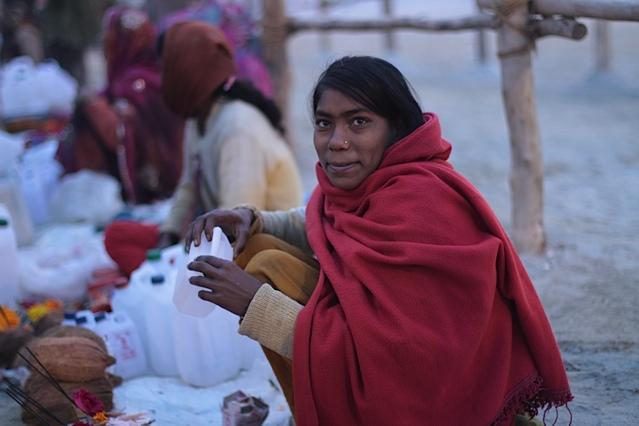 Entrepreneurs take their chances selling wares at unsanctioned, illegal stalls by the side of the road at the Kumbh. They sell everything from beads to bags; this particular woman was selling water.