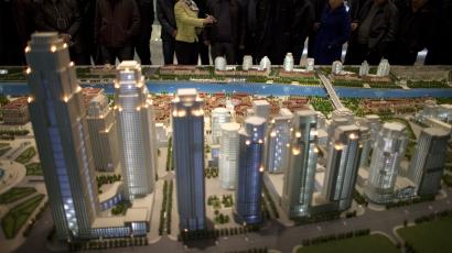 A guide introduces city planning details for a group of visitors at a model of a planned new city zone to be developed by 2020 at the Tianjin Planning Exhibition Hall in Tianjin, China, Tuesday, Feb. 28, 2012. China needs a new economic strategy after three decades of rapid growth and must reduce the dominance of state companies and promote free markets to achieve its goal of becoming a high-income society, the World Bank and Chinese researchers said Monday.