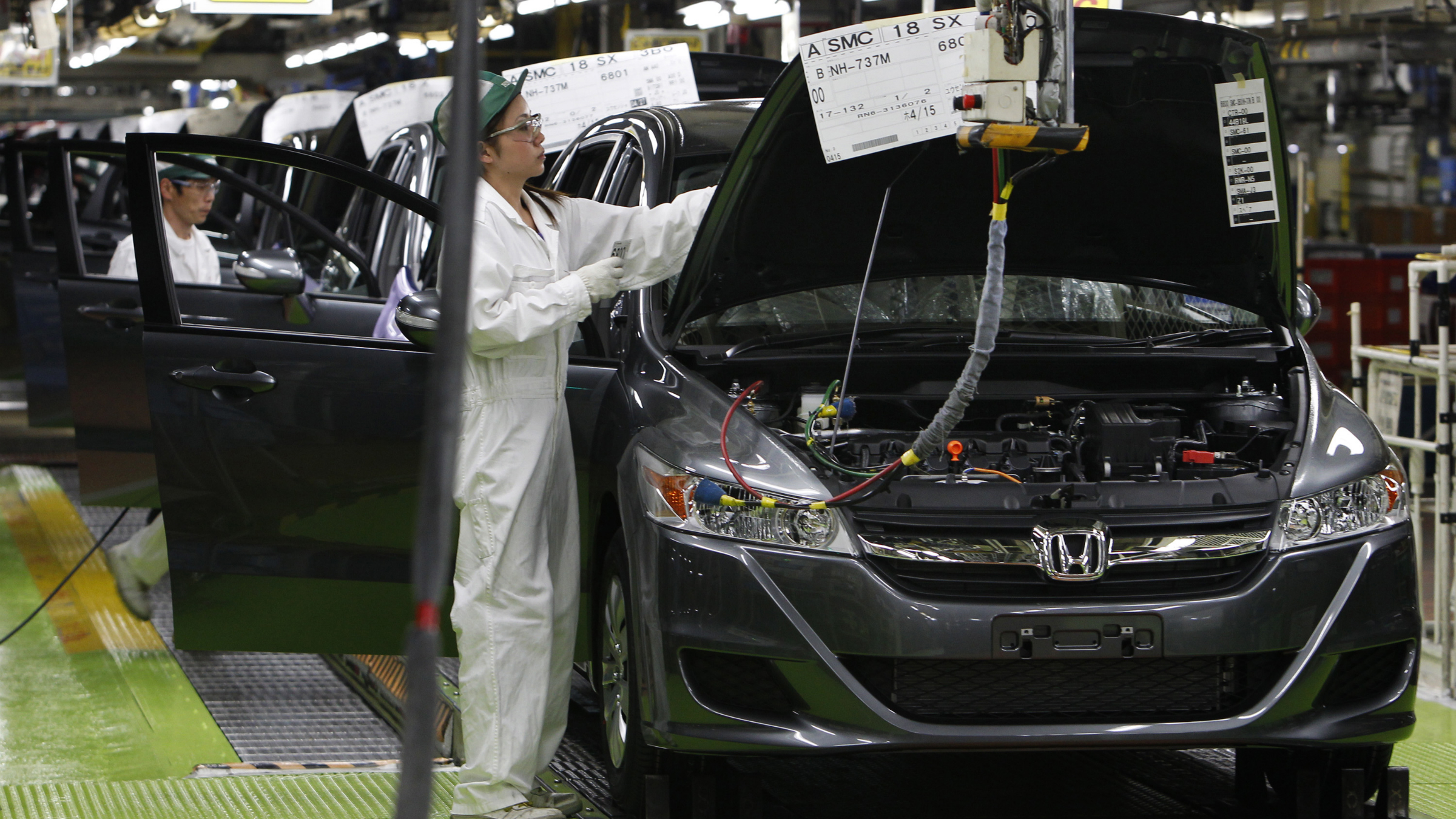 In this April 18, 2011 photo, workers give the final checkup on the cars of Honda Accord Tourer at Honda Motor Co.'s Saitama Factory in Sayama, north of Tokyo, Monday, April 18, 2011 as the Japanese automaker resumed limited production on April 11 at the factory following the March 11 earthquake and tsunami. Honda said Thursday, April 28, 2011 its quarterly profit dropped 38.3 percent due to a slump in car production following last month's disasters.
