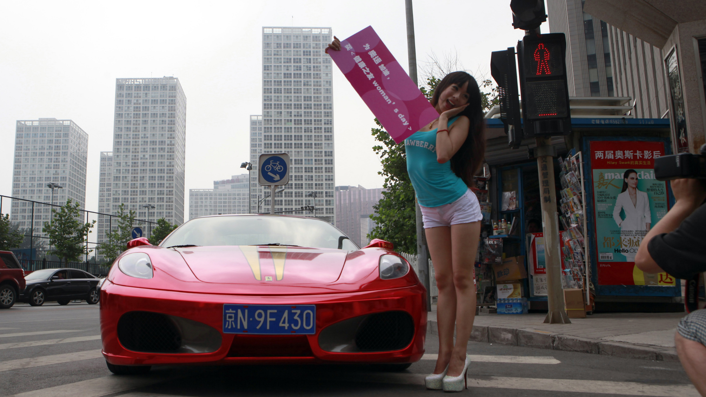 """In this photo taken Wednesday, July 18, 2012, a Chinese model poses next to a luxury sports car during a photo shoot for a Chinese magazine in Beijing, China. The Chinese characters on the board reads """"Support the Olympics, buy the magazine called Woman's Day."""""""