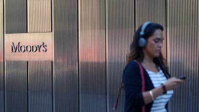A woman with headphones on walks past a Moody's office.