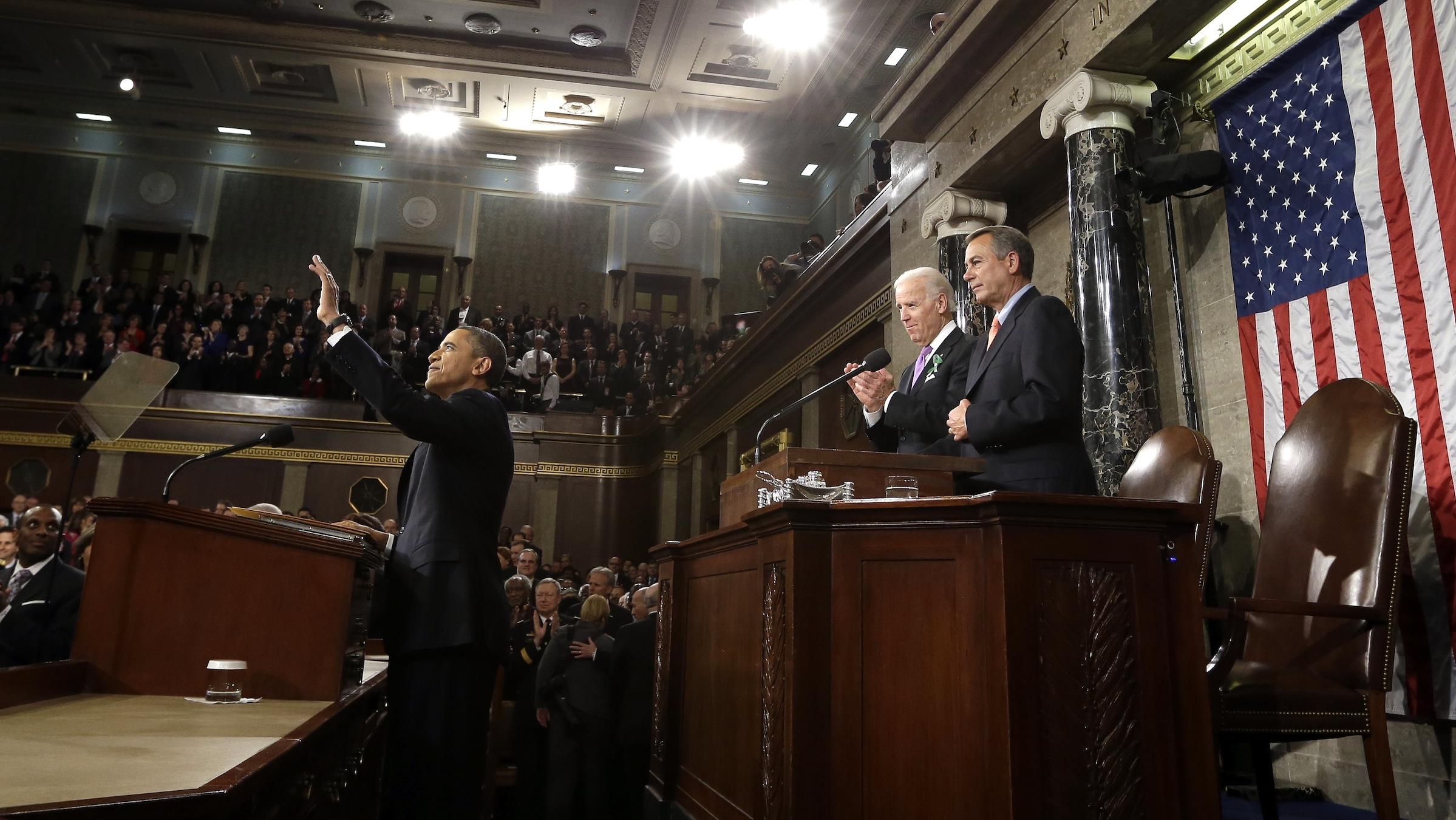 President Barack Obama waves before giving his State of the Union address during a joint session of Congress on Capitol Hill in Washington, Tuesday Feb. 12, 2013. Vice President Joe Biden and House Speaker John Boehner of Ohio stand behind the president. (AP Photo/Charles Dharapak, Pool)