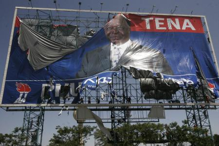 Supporters of the Orange Democratic Movement tear down a poster of Kenyan President Mwai Kibaki and head of the ruling Party of National Unity, Monday, Dec. 24, 2007.