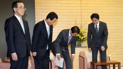 "Japanese Prime Minister Shinzo Abe, right, takes a seat as he arrives for meeting with Finance Minister Taro Aso, center, Economics Minister Akira Amari, second from left, and Bank of Japan Gov Masaaki Shirakawa, at the prime minister's official residence in Tokyo, Tuesday, Jan. 22, 2013. Japan's Prime Minister Shinzo Abe declared a ""monetary regime change"" Tuesday as the central bank bowed to government pressure, setting a 2 percent inflation target aimed at helping the country emerge from its prolonged bout of deflation."