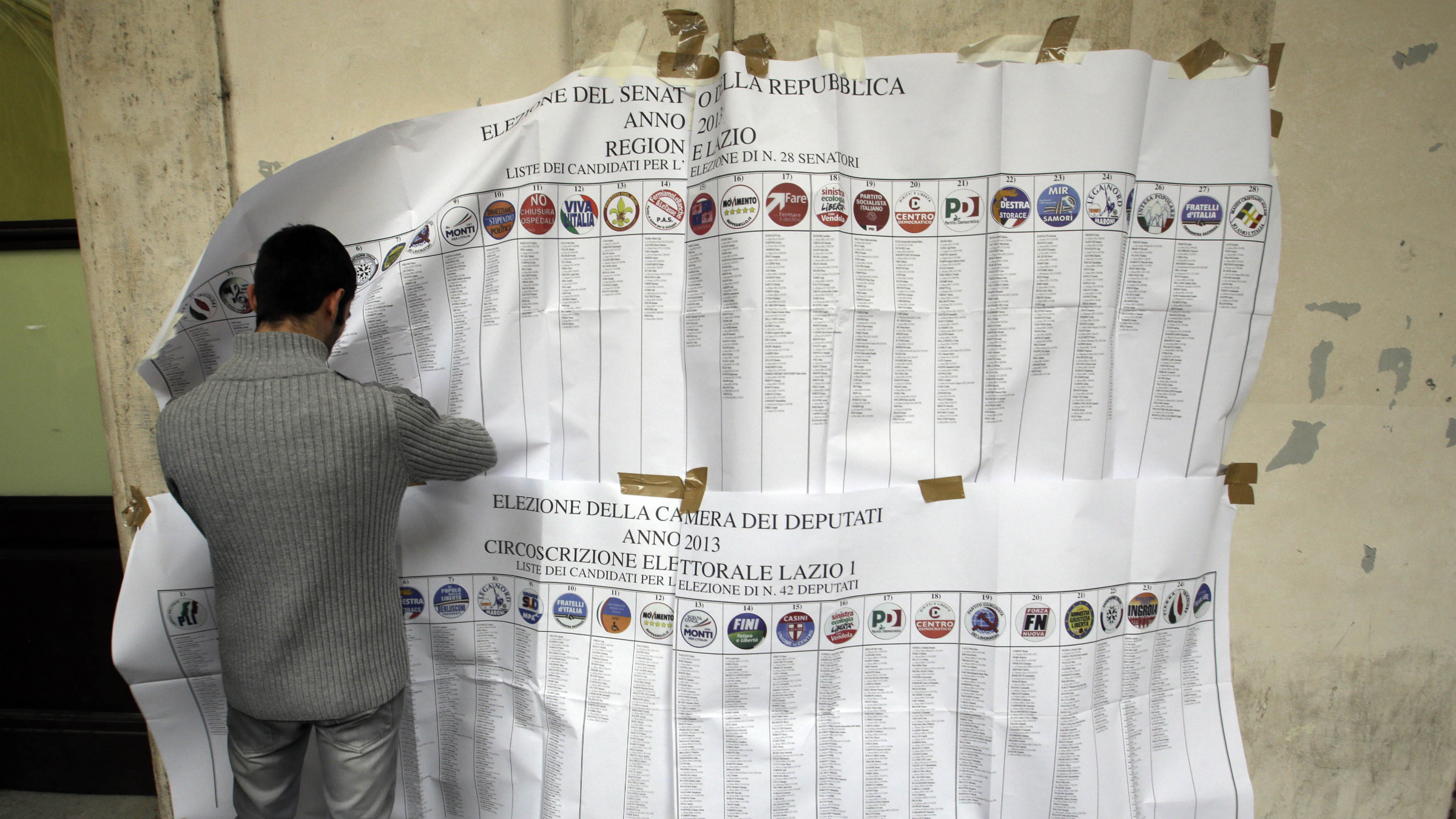 Lists of candidates are removed at a polling station in Rome, Monday, Feb. 25, 2013. Italy's crucial elections appear to be heading toward gridlock, initial results show, with the center-left forces of Pier Luigi Bersani headed toward victory in the lower house of Parliament and the camp of former premier Silvio Berlusconi gaining the upper hand in the equally powerful Senate. The upstart protest campaign of comic-turned-politician Beppe Grillo was also showing a stunningly strong result in both houses of the legislature, confirming its surprise role as a force in Italian politics.