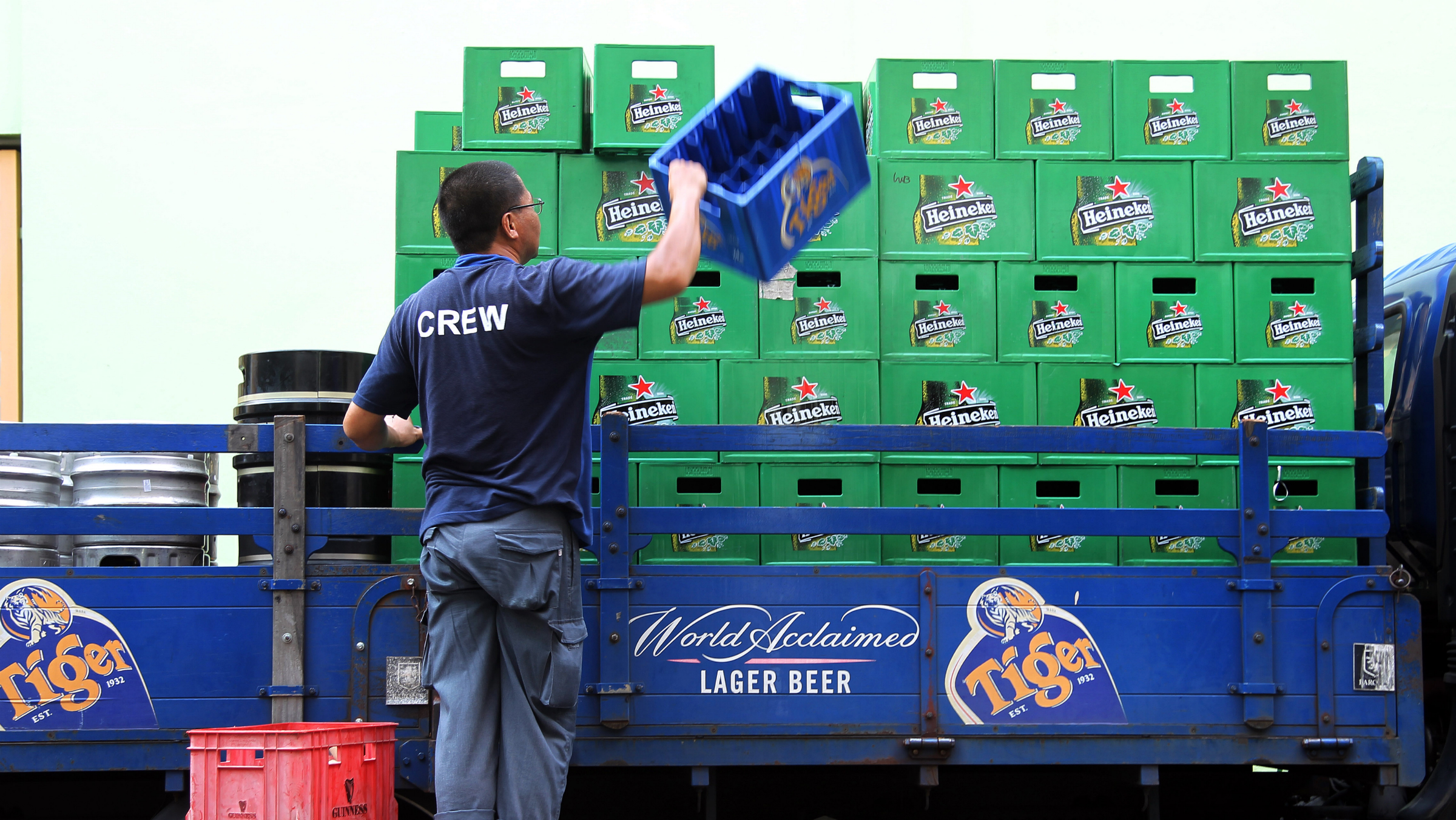 In this Aug. 14, 2012 file photo, a worker unloads a truck delivering Heineken and Tiger beer to a pub before its opening hours in Singapore. Heineken NV, based in Amsterdam, says it has sealed a deal giving it control over the Tiger beer brand, paying €4.7 billion ($6.1 billion) to significantly expand its presence in Asia. Shareholders of Singapore-based drinks conglomerate Fraser & Neave agreed Friday, Sept. 28 to sell its 39.7 percent stake in Asian Pacific Breweries, the owner of the Tiger brand, to Heineken. After Friday's deal, Heineken controls 95 percent of APB.