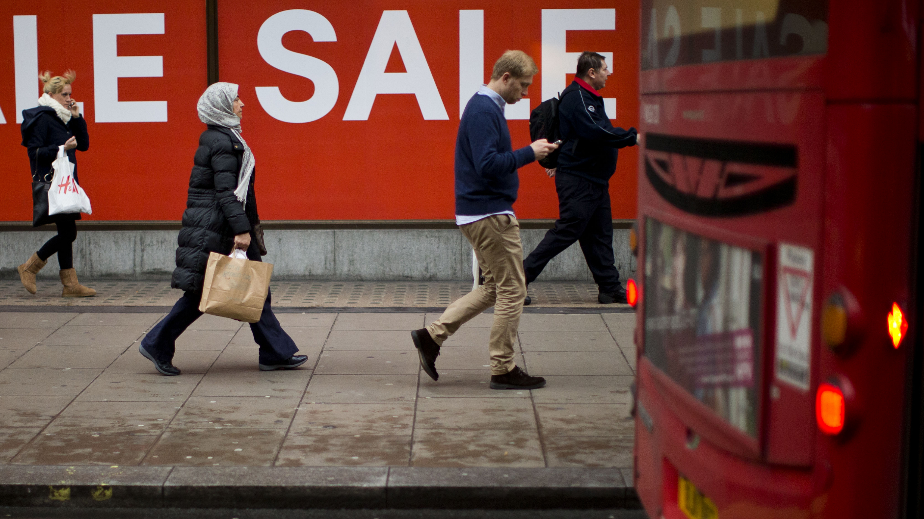 People walk past sale signs on Oxford Street in London, Monday, Dec. 24, 2012. Sales in some UK stores began on Christmas Eve.