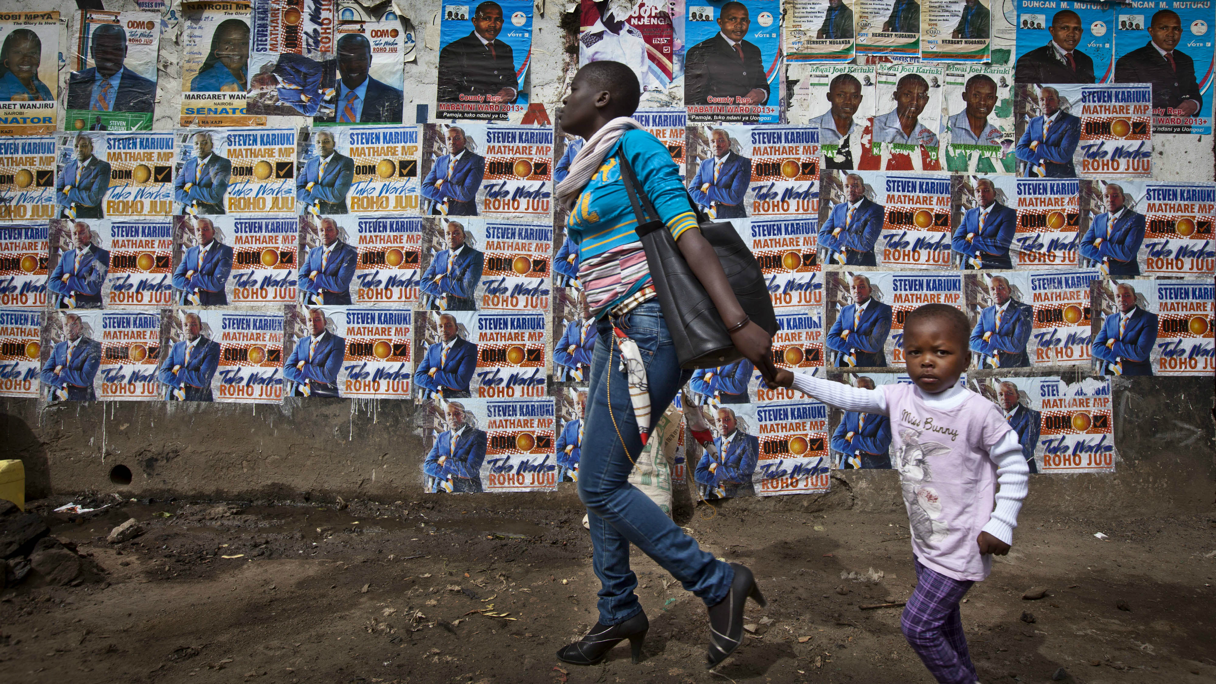 A mother and her child walk past a wall plastered with election campaigning posters in the Mathare slum of Nairobi.