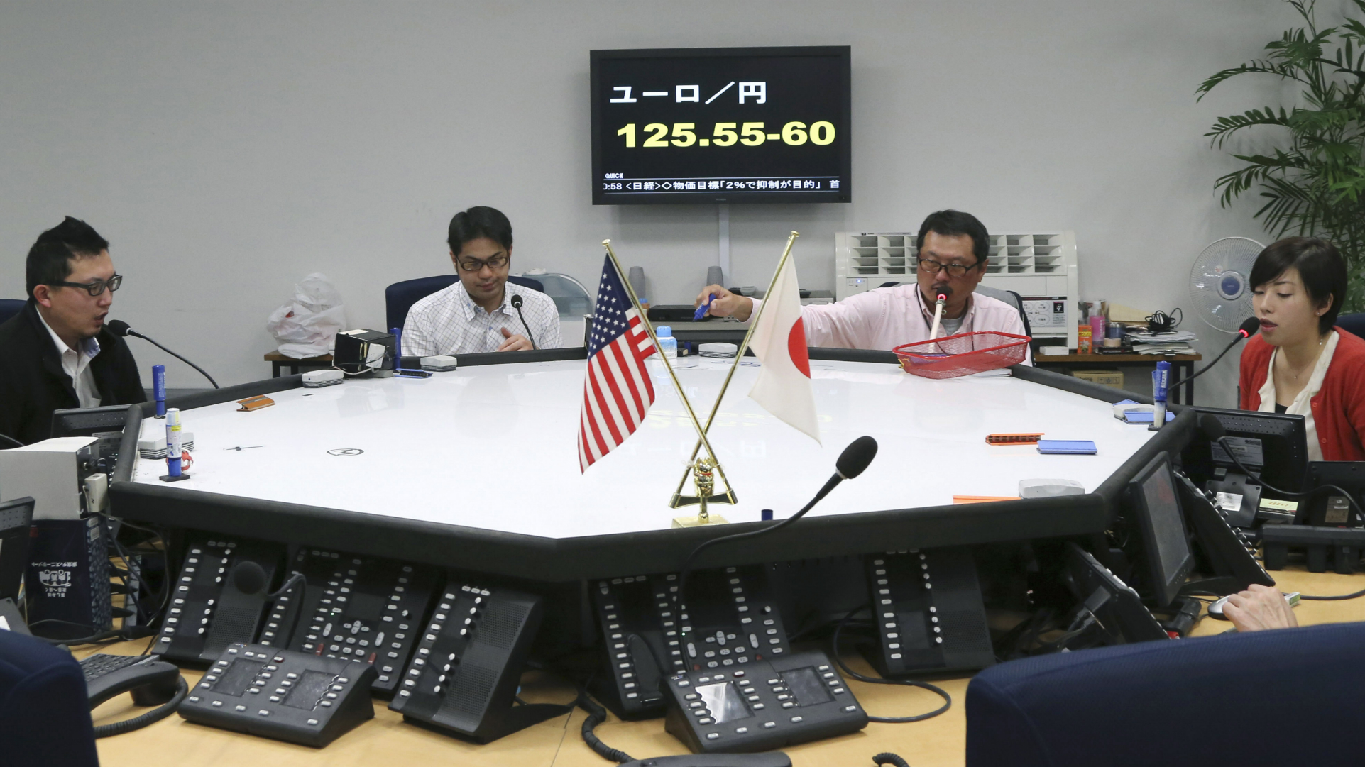 Foreign exchange brokers work in front of a screen displaying the day's euro rate equaling between 125.55 - 125.60 yen, at an office in Tokyo, Monday, Feb. 18, 2013. Last week, the yen fell to a near three-year low against the dollar and the euro.