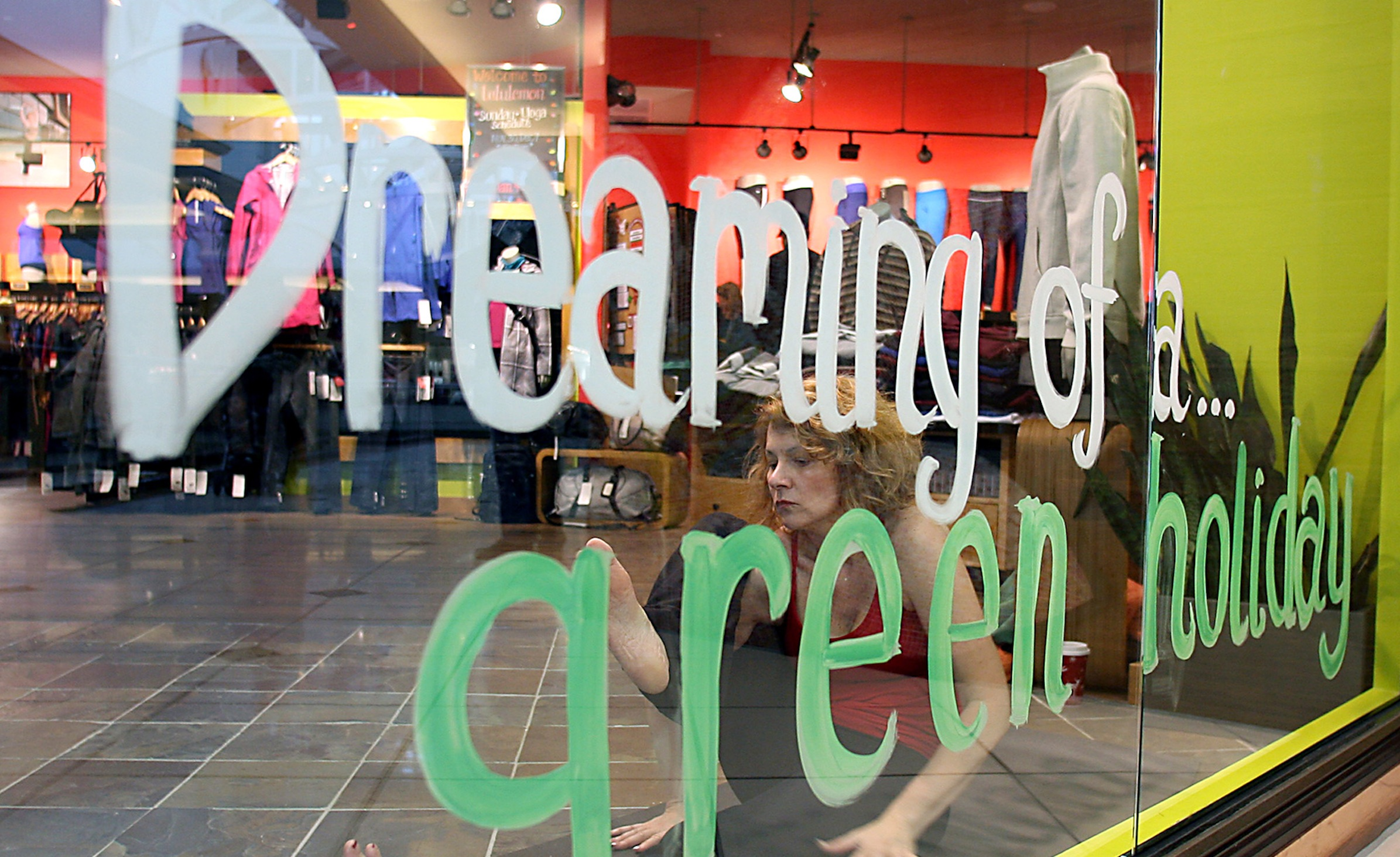 Yoga trainer Natalie Mitoraj of Rochester, Mich. performs yoga for passing shoppers behind painted glass with the sentiment 'Dreaming of a green holiday', at the LuluLemon Athletica store located at the Somerset Collection in Troy, Mich. during  Black Friday Nov. 28, 2008.