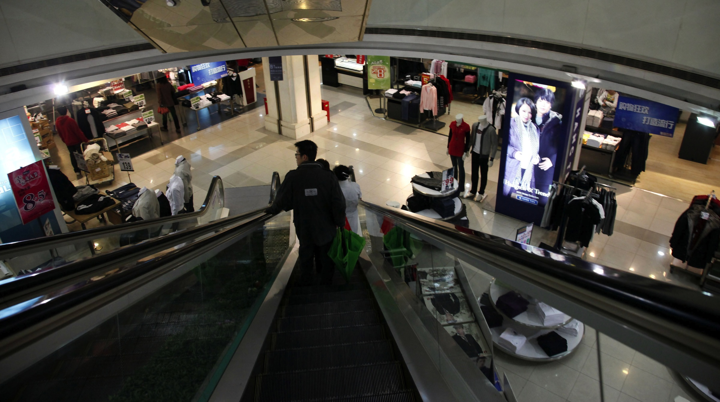 A couple of customers take the escalater to a rather empty shopping mall Friday March 13, 2009 in Shanghai, China. Chinese Premier Wen Jiabao stressed that a half-trillion-dollar stimulus program would revive the buoyant growth dragged down by the global downturn and create jobs and provide social welfare to cope with worsening unemployment. (AP photo/Eugene Hoshiko)