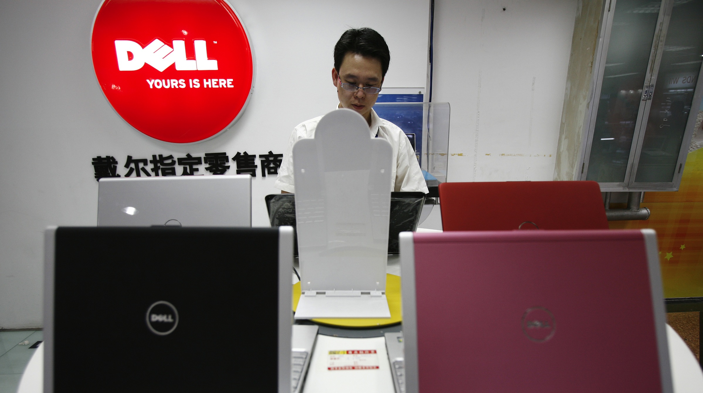 A man works behind Dell laptops on display at a computer store in Beijing, China, Tuesday, June 30, 2009. A California company that says its software was illegally used in Beijing's new Internet filter threatened possible legal action as PC makers faced a Wednesday deadline to supply the system with computers. U.S. trade officials and industry and free-speech groups have also appealed to Beijing to revoke its order, which requires suppliers to pre-install the Green Dam filtering software or include it on a disk with each PC sold from July 1. (AP Photo/Greg Baker)