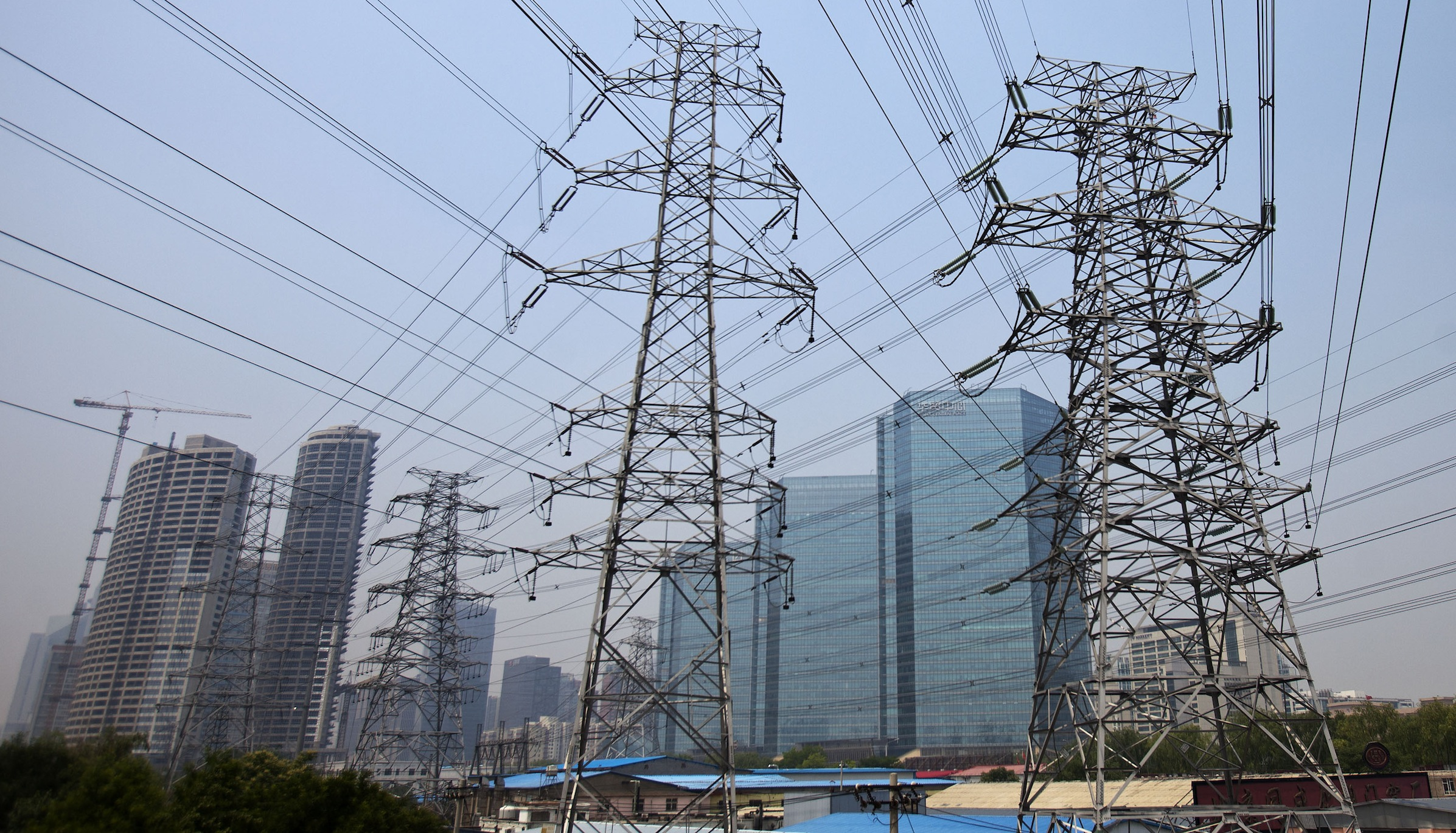 In this photo taken on Friday, May 27, 2011, electric pylons are seen against the commercial buildings at the Central Business District in Beijing, China. China has raised power prices for some industrial users in an apparent effort to promote consumption and encourage utilities to generate more electricity as parts of the country grapple with their worst shortages in years. (AP Photo/Andy Wong)