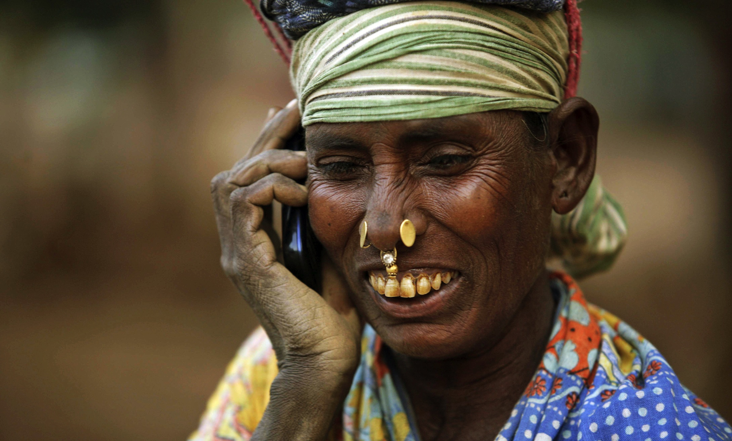 An Indian daily wage laborer talks on a mobile phone, at a construction site in Bhubaneshwar, India, Thursday, Feb. 2, 2012. India's top court ordered the government on Thursday to cancel 122 cellphone licenses granted to companies during an irregular sale of spectrum that has been branded one of the largest scandals in India's history. (AP Photo/Biswaranjan Rout)