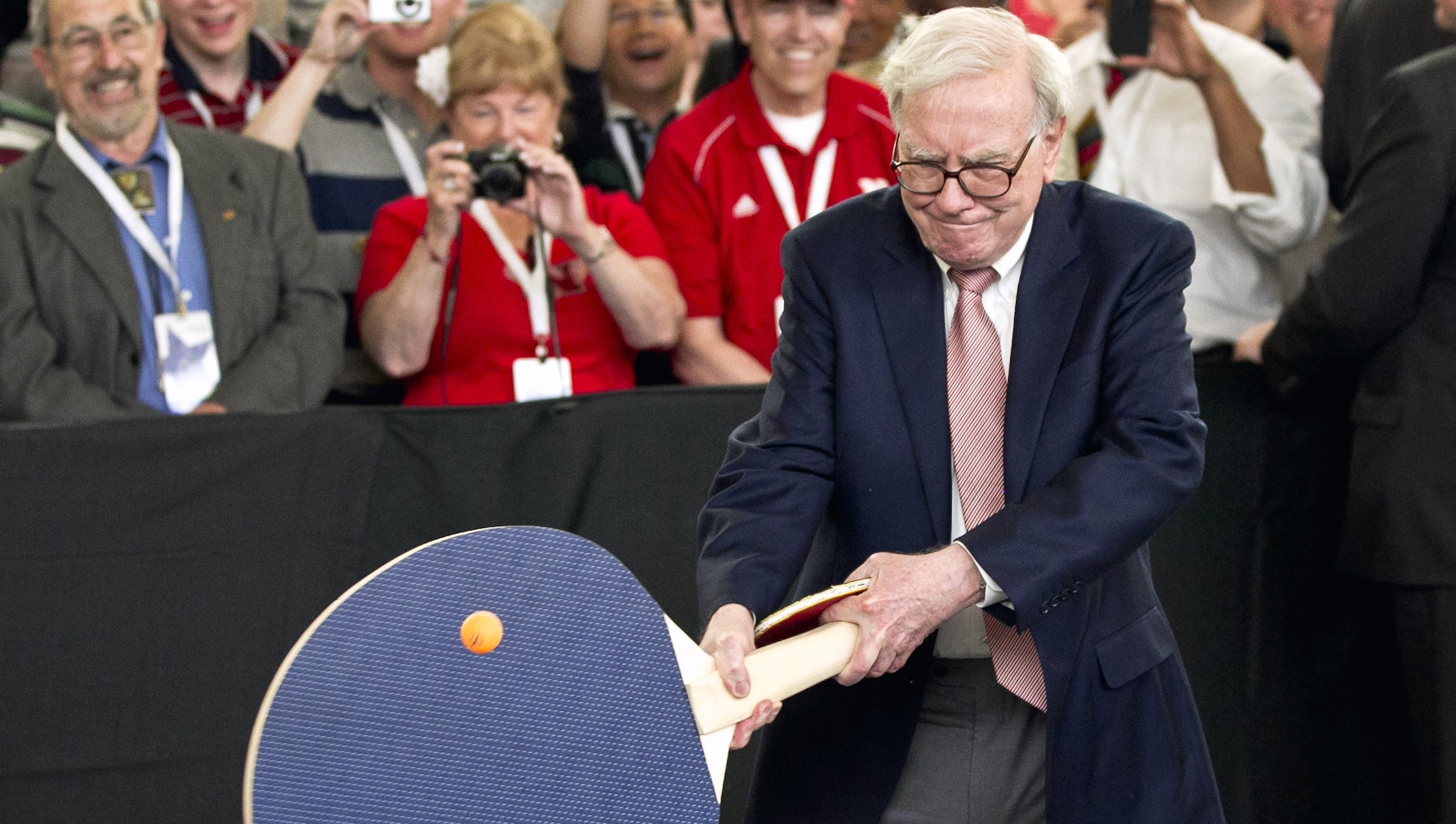 Shareholders watch as Warren Buffett, chairman and CEO of Berkshire Hathaway, deploys an oversize bat against table tennis prodigy Ariel Hsing in Omaha, Neb., Sunday, May 6, 2012. Berkshire Hathaway is holding its annual shareholders meeting this weekend. (AP Photo/Nati Harnik)