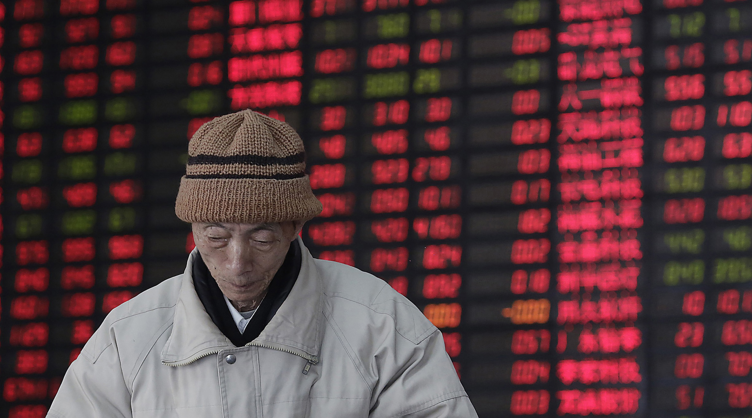 An investor walks in front of the stock price monitor at a private securities company on Wednesday March 6, 2013. The Dow's new all-time high and better economic data from the United States propelled Asian stock markets higher Wednesday. (AP Photo/Eugene Hoshiko)