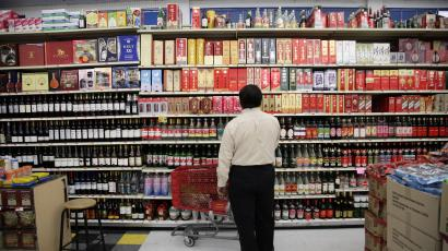 In this April 10, 2012, photo, a shopper looks at the section of imported hard liquor at a Chinese market in Monterey Park, Calif. When Walmart announced plans to put one of its sprawling outlets in Chinatown, alarms were quickly sounded by people fearful that a chain superstore would destroy the character of one of the nation's oldest, largest and most historic Chinatowns. These days New Chinatown, as it was called then, finds itself increasingly surrounded by multi-ethnic neighborhoods and high-density residential developments like the building that would house the Walmart store on its ground floor. (AP Photo/Jae C. Hong