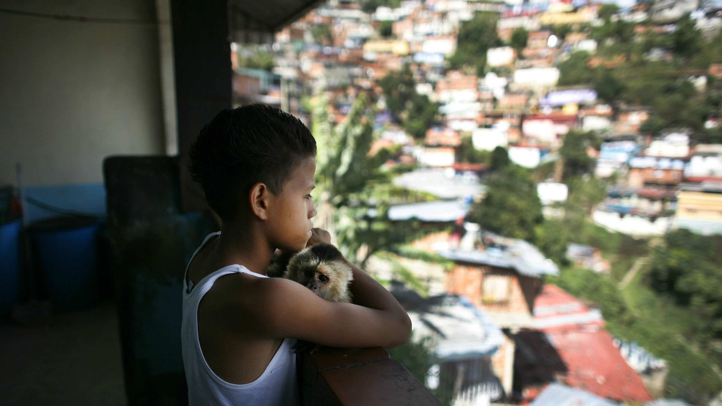 A boy looks out over the slums of Caracas