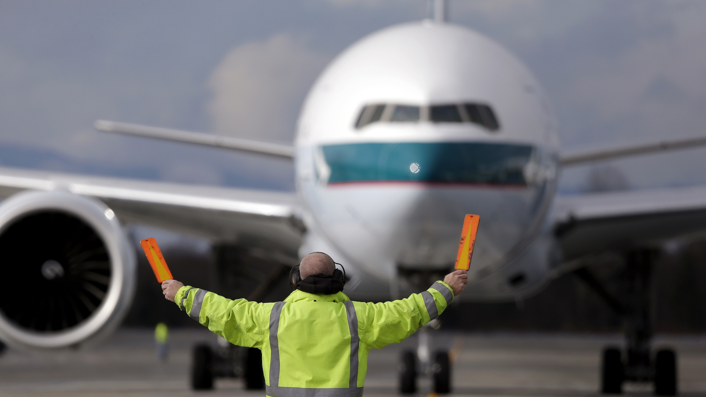 A Boeing 777-367 (ER) Cathay Pacific jet is guided to a parking spot by a marshaller at Paine Field Tuesday, Feb. 5, 2013, in Everett, Wash. (AP Photo/Elaine Thompson)