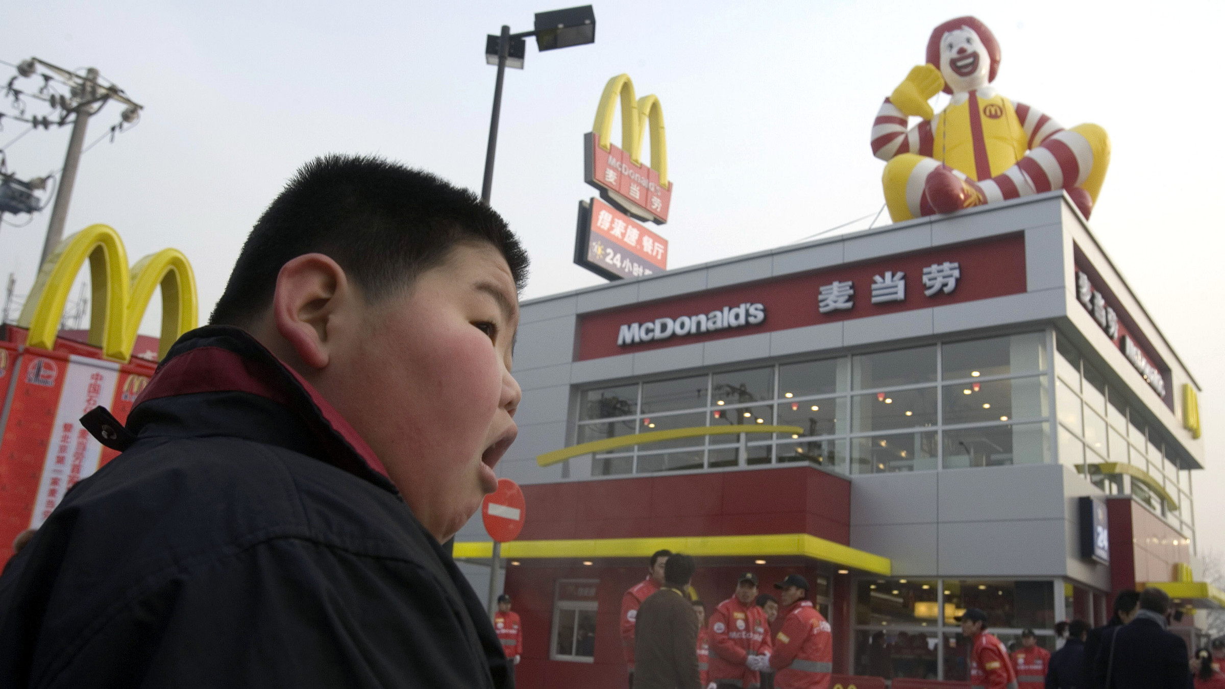 A Chinese child looks on at a new McDonald's drive-thru outlet built next to a gas station in Beijing, China, Friday, Jan. 19, 2007.