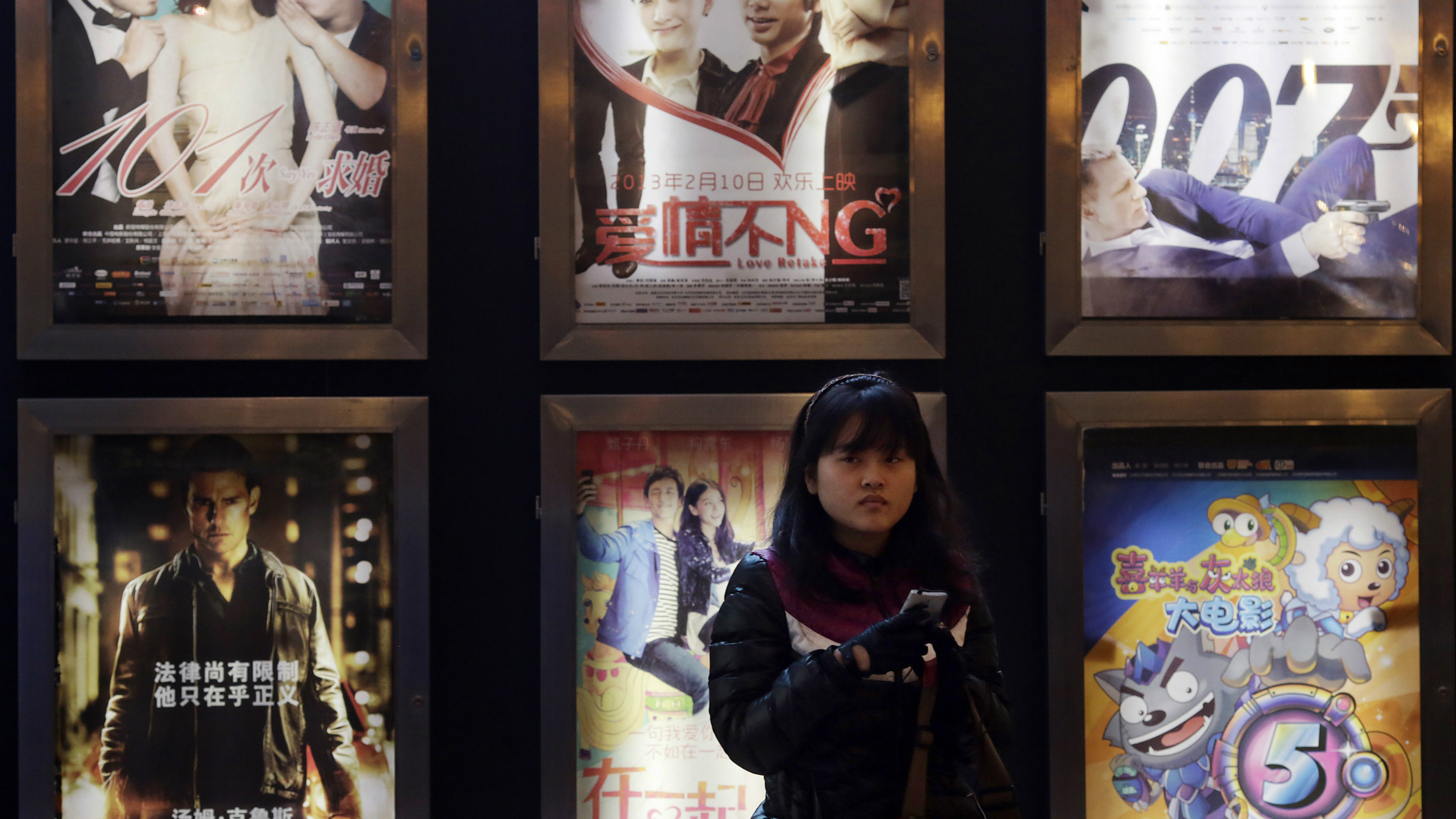 A woman stands in front of the advertisements of Chinese and foreign films on showing at a movie theater Wednesday Feb. 13, 2013 in Shanghai.